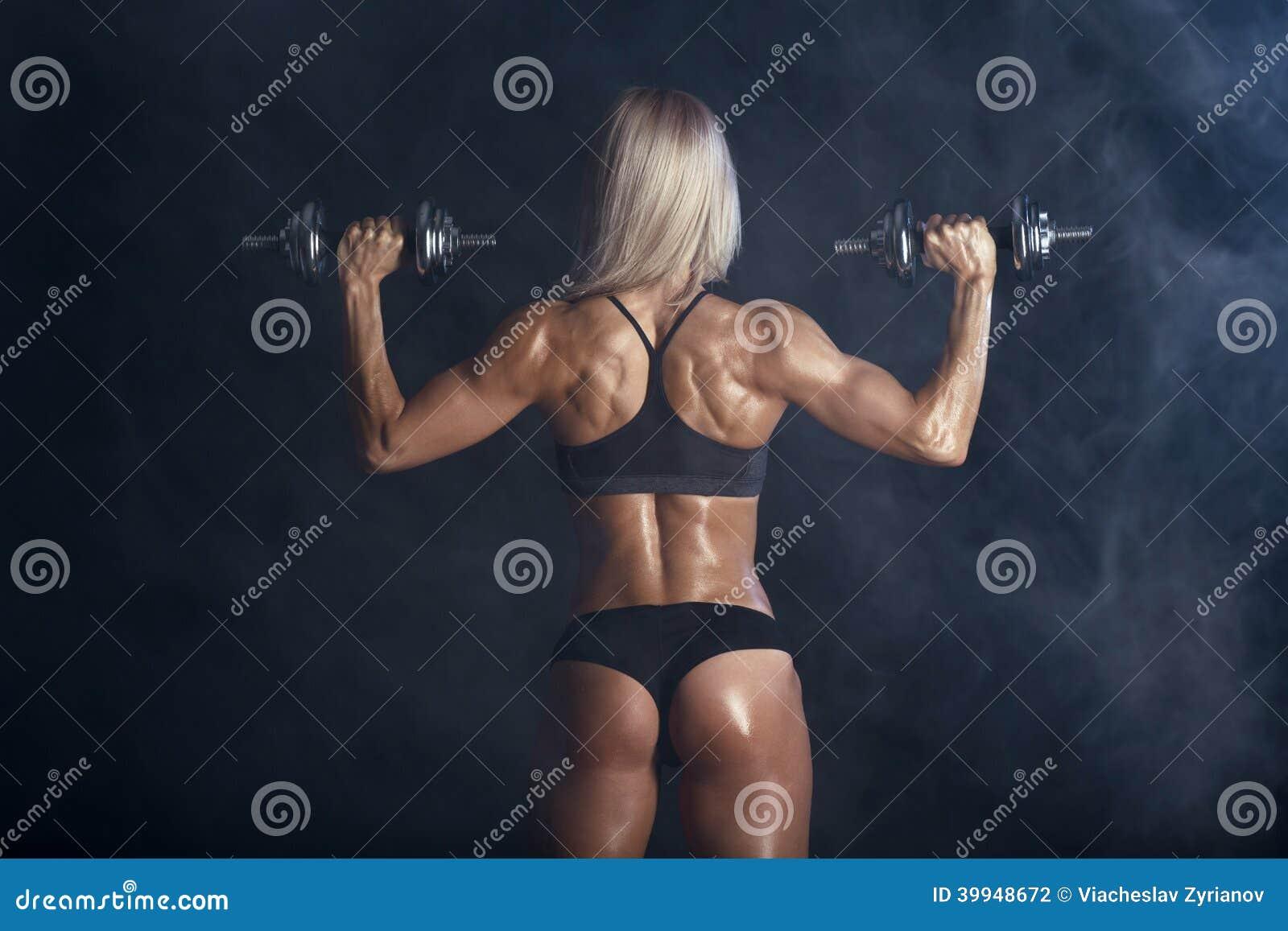 Η ισχυρή προκλητική γυναίκα εκπαιδεύει με τα barbells