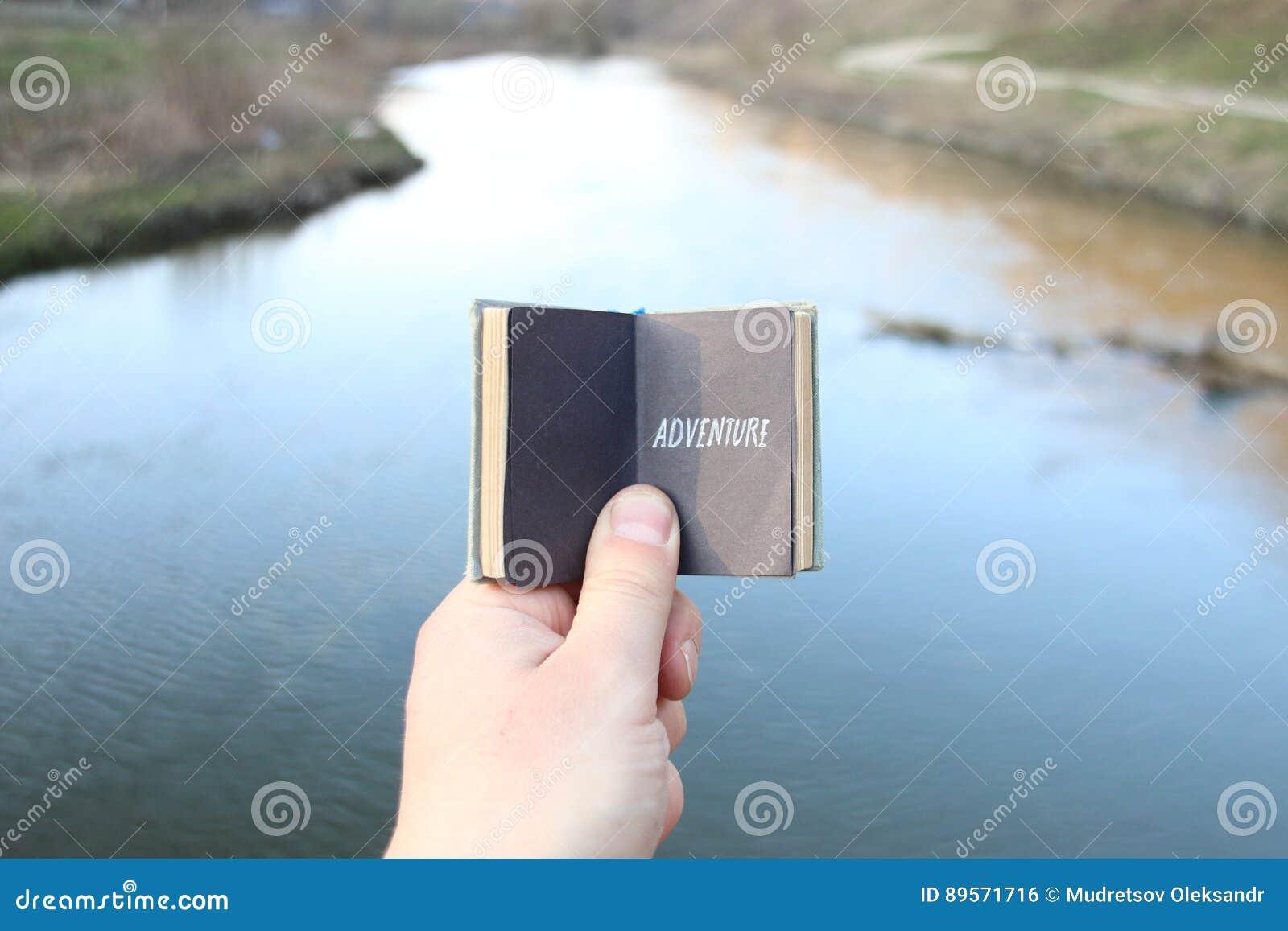 Η ιδέα περιπέτειας, ταξιδιώτης κρατά ένα βιβλίο με το κείμενο
