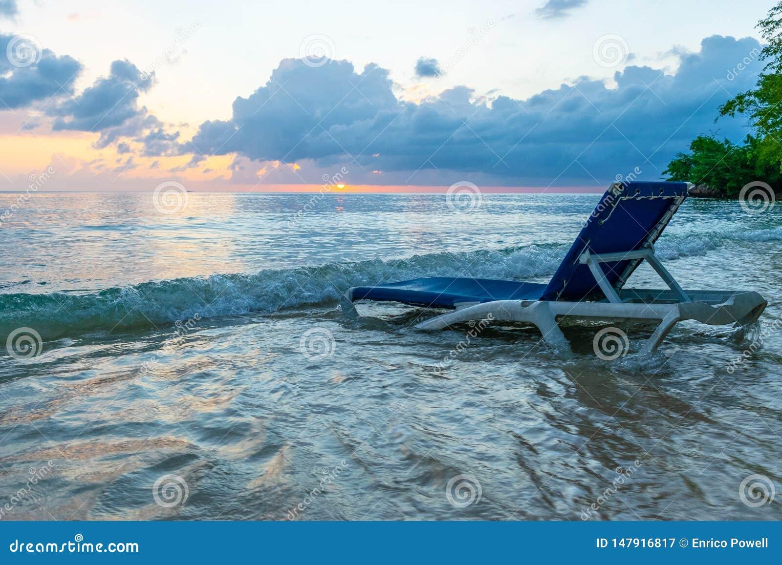 Η καρέκλα σαλονιών παραλιών στο νερό στην όμορφη άσπρη ακτή άμμου ως φως των ουρανών αρχίζει να καίγεται στο ηλιοβασίλεμα