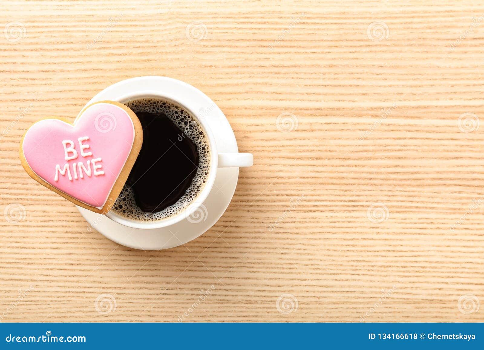 Η καρδιά διαμόρφωσε το μπισκότο με τη γραπτή φράση είναι ορυχείο και φλιτζάνι του καφέ στο ξύλινο υπόβαθρο, τοπ άποψη