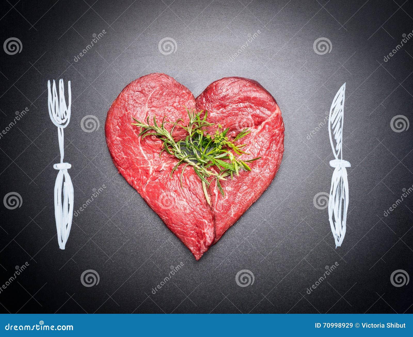 Η καρδιά διαμόρφωσε την ακατέργαστη μπριζόλα του κρέατος Αγάπη κρέατος με τα χρωματισμένα μαχαιροπήρουνα: δίκρανο και μαχαίρι Σκο