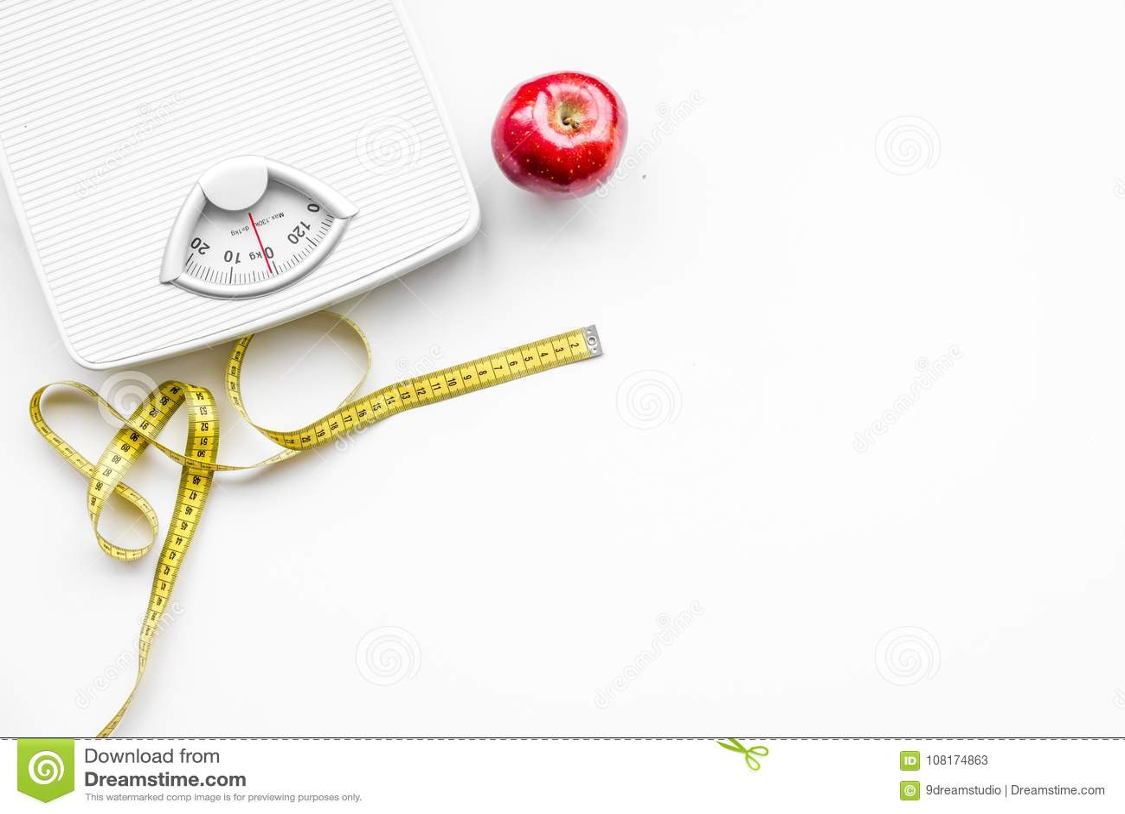 Η κατάλληλη διατροφή για χάνει το βάρος Κλίμακα, που μετρά την ταινία, μήλο στο άσπρο διάστημα άποψης υποβάθρου τοπ για το κείμεν