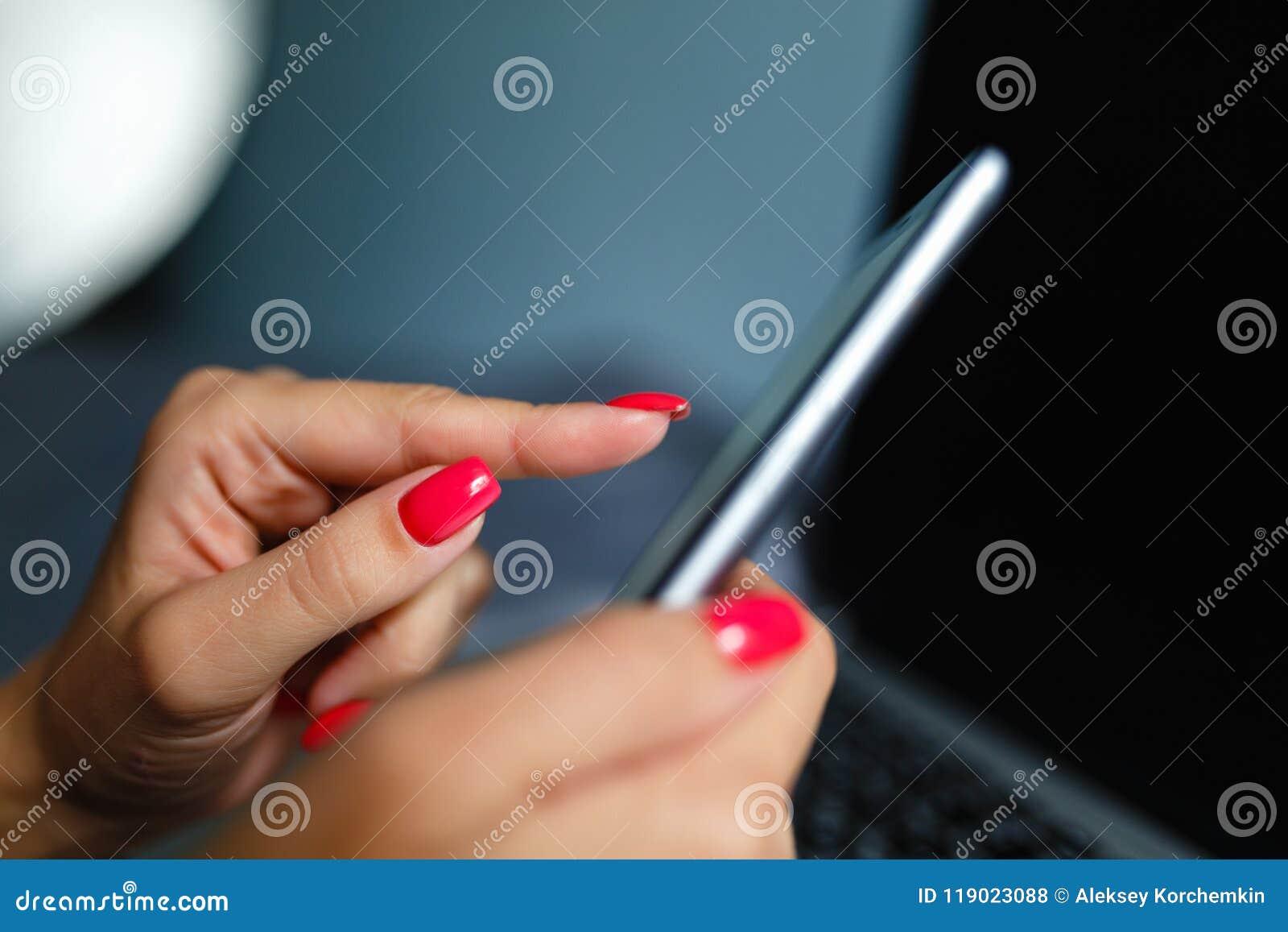 Η κινηματογράφηση σε πρώτο πλάνο ενός κοριτσιού με ένα συμπαθητικό μανικιούρ αγγίζει την οθόνη του smartphone στο υπόβαθρο ενός l