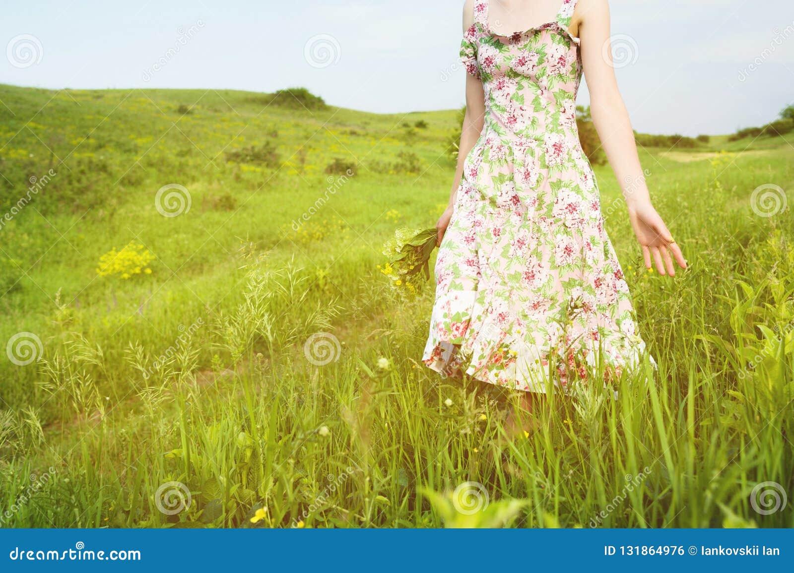 Η κινηματογράφηση σε πρώτο πλάνο στους ώμους από κάτω από ένα νέο κορίτσι με μια ανθοδέσμη των άγριων λουλουδιών στο χέρι της περ