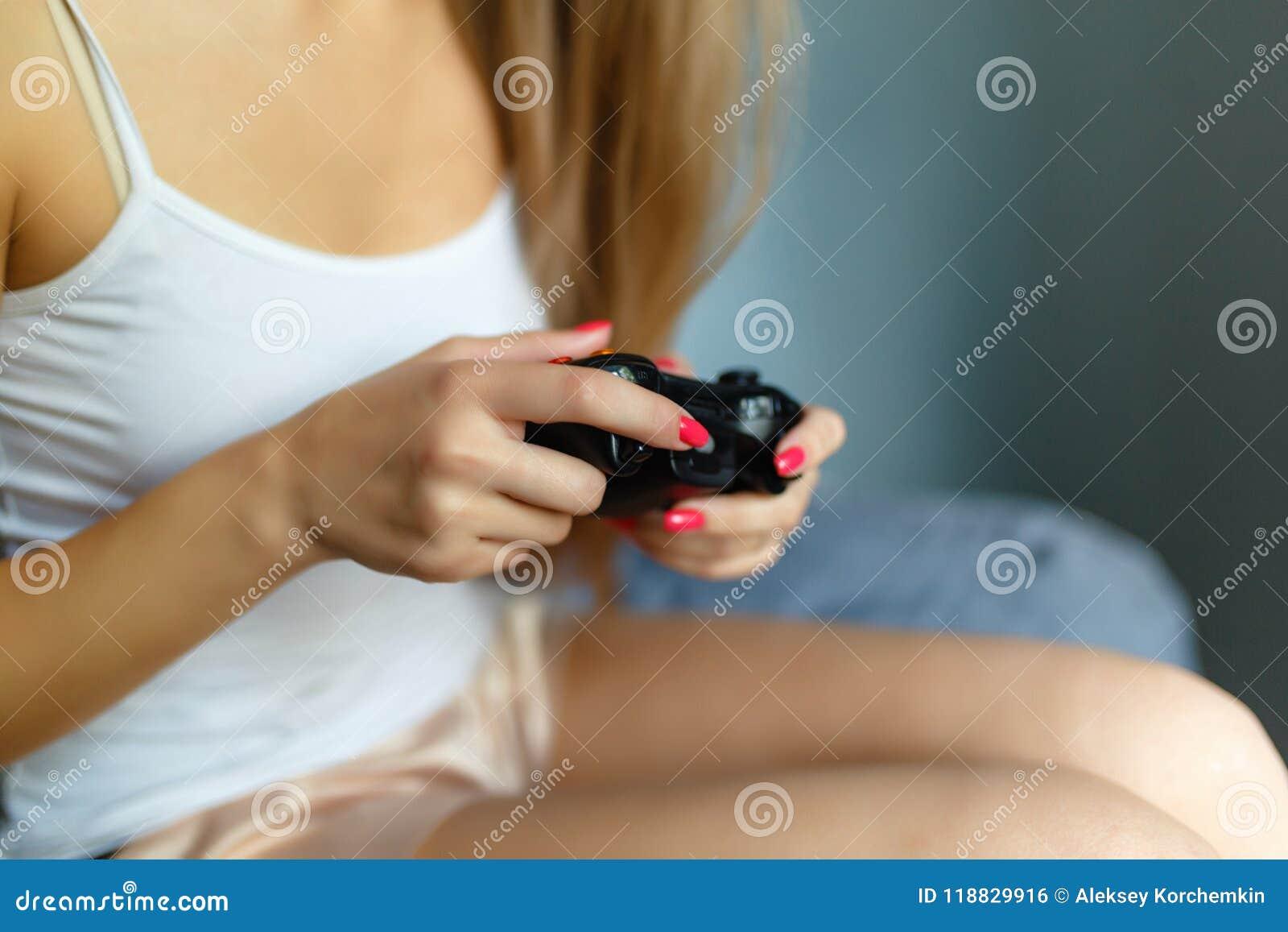 Η κινηματογράφηση σε πρώτο πλάνο του ξανθού κοριτσιού χεριών με τα διαθέσιμα παίζοντας τηλεοπτικά παιχνίδια gamepad παρηγορεί στο