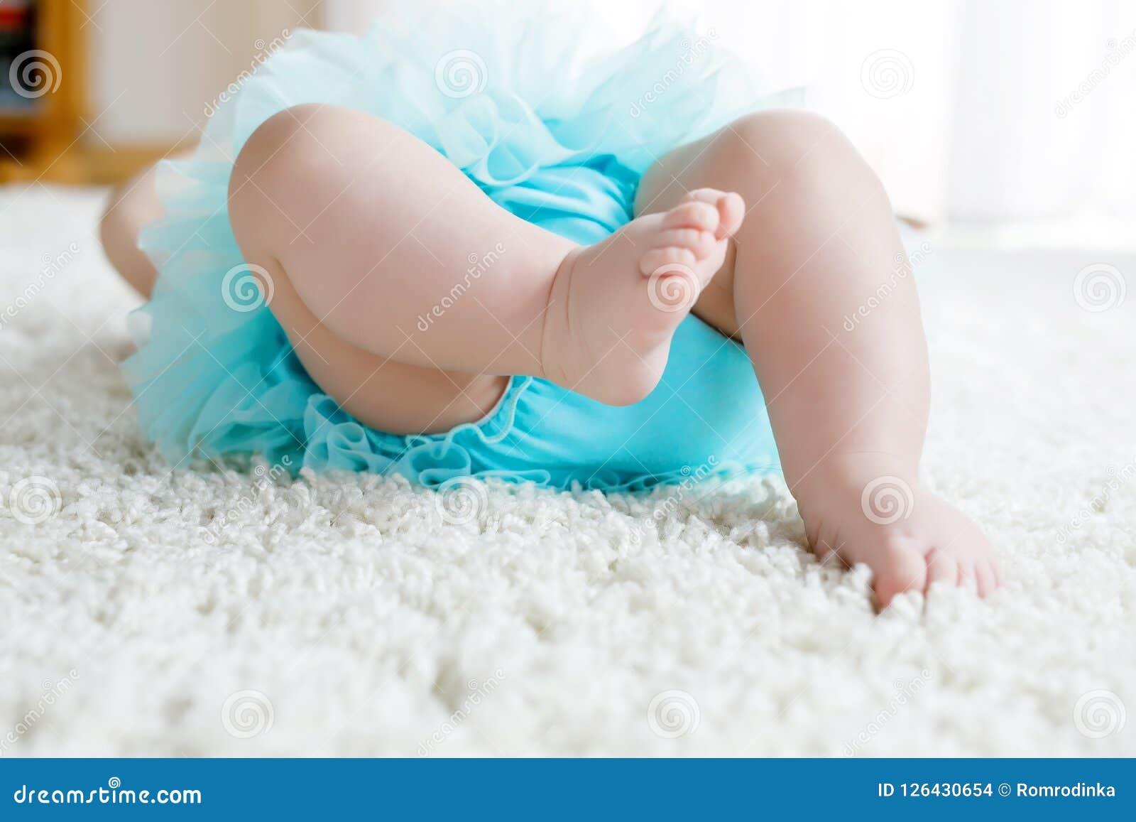 Η κινηματογράφηση σε πρώτο πλάνο των ποδιών και τα πόδια του κοριτσάκι στο άσπρο υπόβαθρο που φορά το τυρκουάζ tutu περιζώνουν