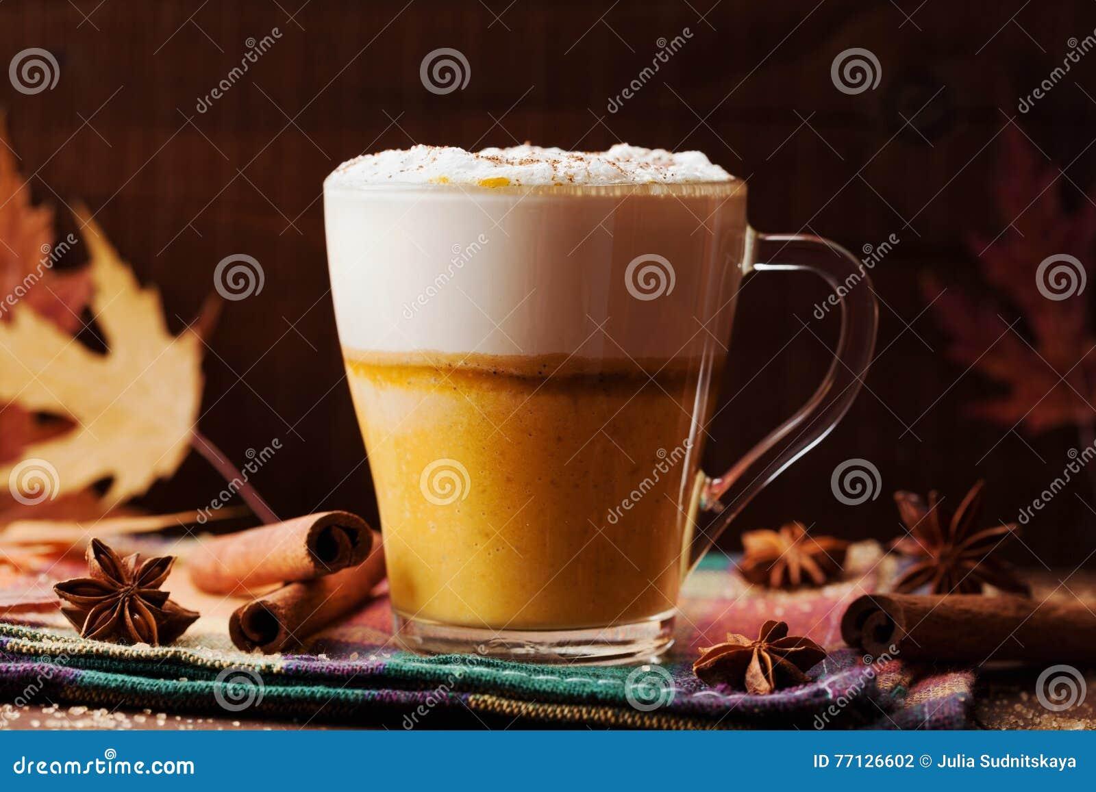 Η κολοκύθα καρύκευσε latte ή καφές σε ένα γυαλί σε έναν ξύλινο εκλεκτής ποιότητας πίνακα Ζεστό ποτό φθινοπώρου ή χειμώνα