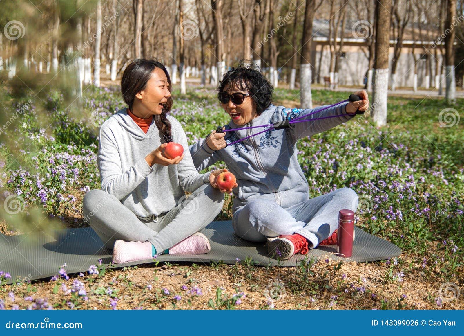 Η κόρη βοηθά τη μητέρα της με τις ασκήσεις στο πάρκο