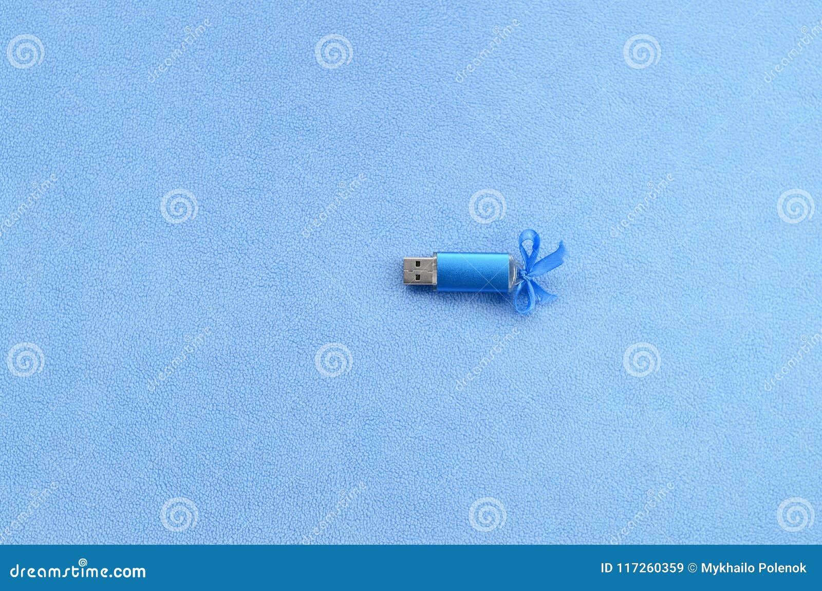 Η λαμπρή μπλε κάρτα αστραπιαίας σκέψης usb με ένα μπλε τόξο βρίσκεται σε ένα κάλυμμα του μαλακού και γούνινου ανοικτό μπλε υφάσμα
