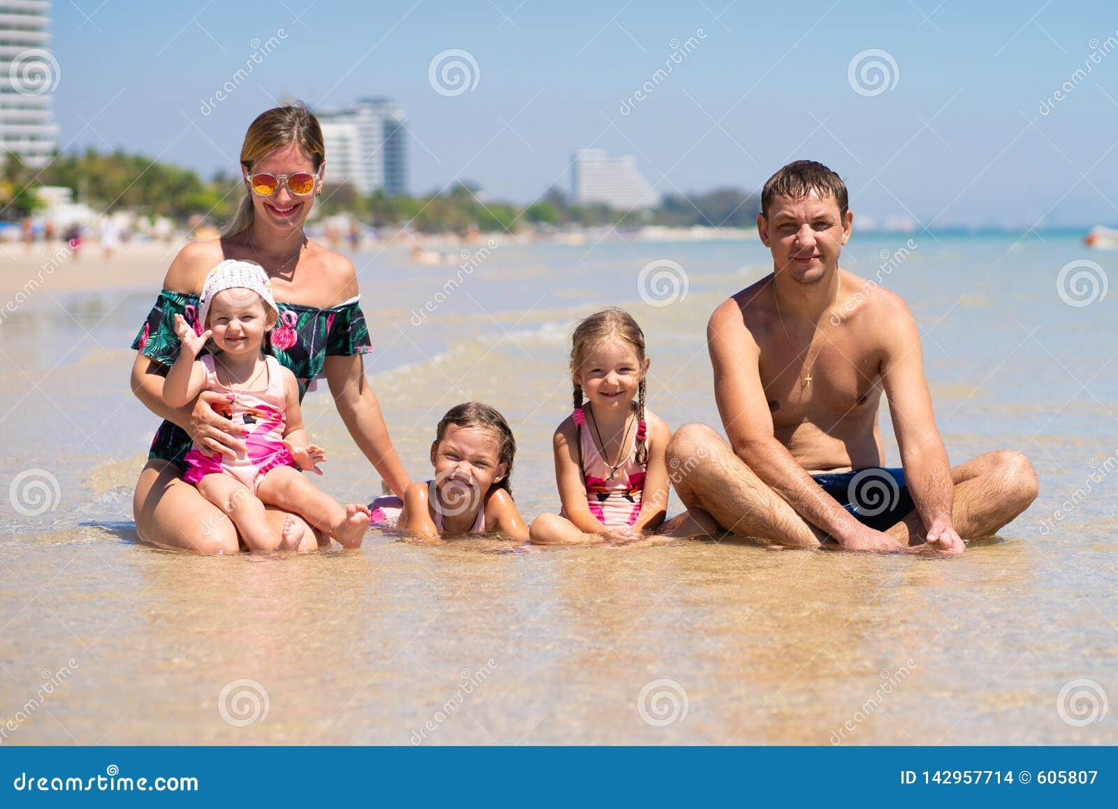 Η μεγάλη ευτυχής οικογένεια έχει τη διασκέδαση στην παραλία έννοια μιας μεγάλης οικογένειας εν πλω Μόδα παραλιών
