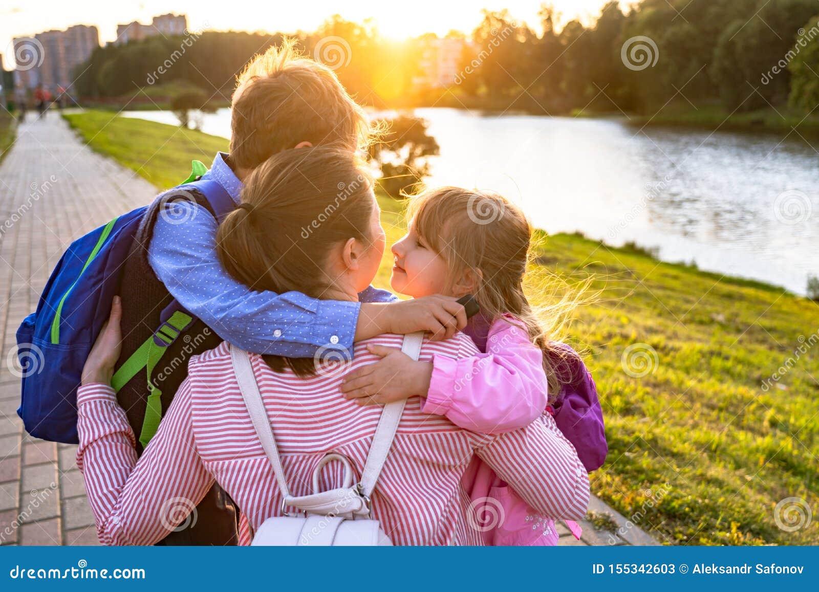 Η μητέρα αγκαλιάζει το γιο και η κόρη στέλνει τα παιδιά στο σχολείο