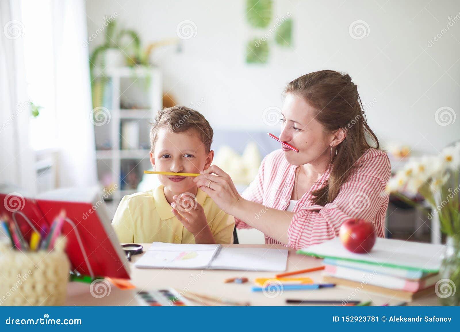 Η μητέρα βοηθά το γιο για να κάνει τα μαθήματα εγχώρια εκπαίδευση, εγχώρια μαθήματα η γυναίκα είναι δεσμευμένη με το παιδί, ελέγχ