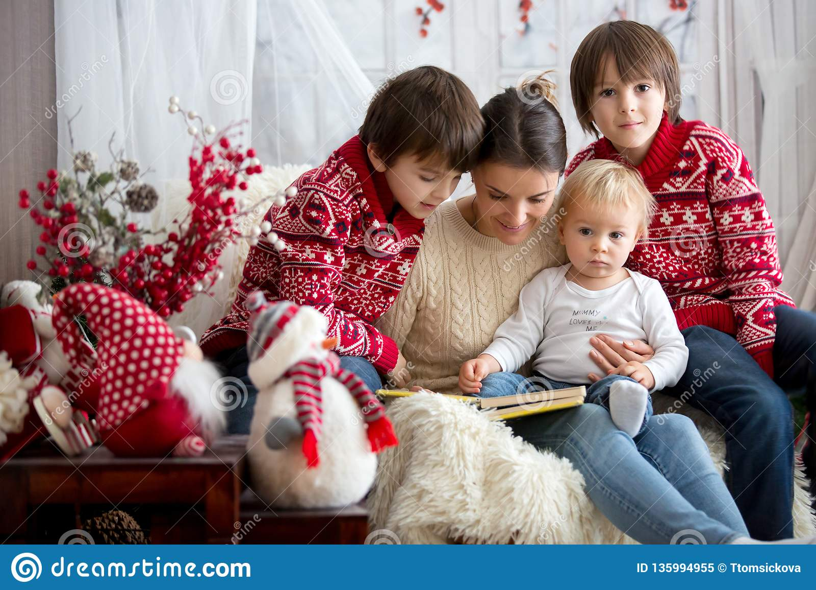 Η μητέρα διαβάζει το βιβλίο στους γιους της, παιδιά που κάθονται στην άνετη πολυθρόνα μια χιονώδη χειμερινή ημέρα