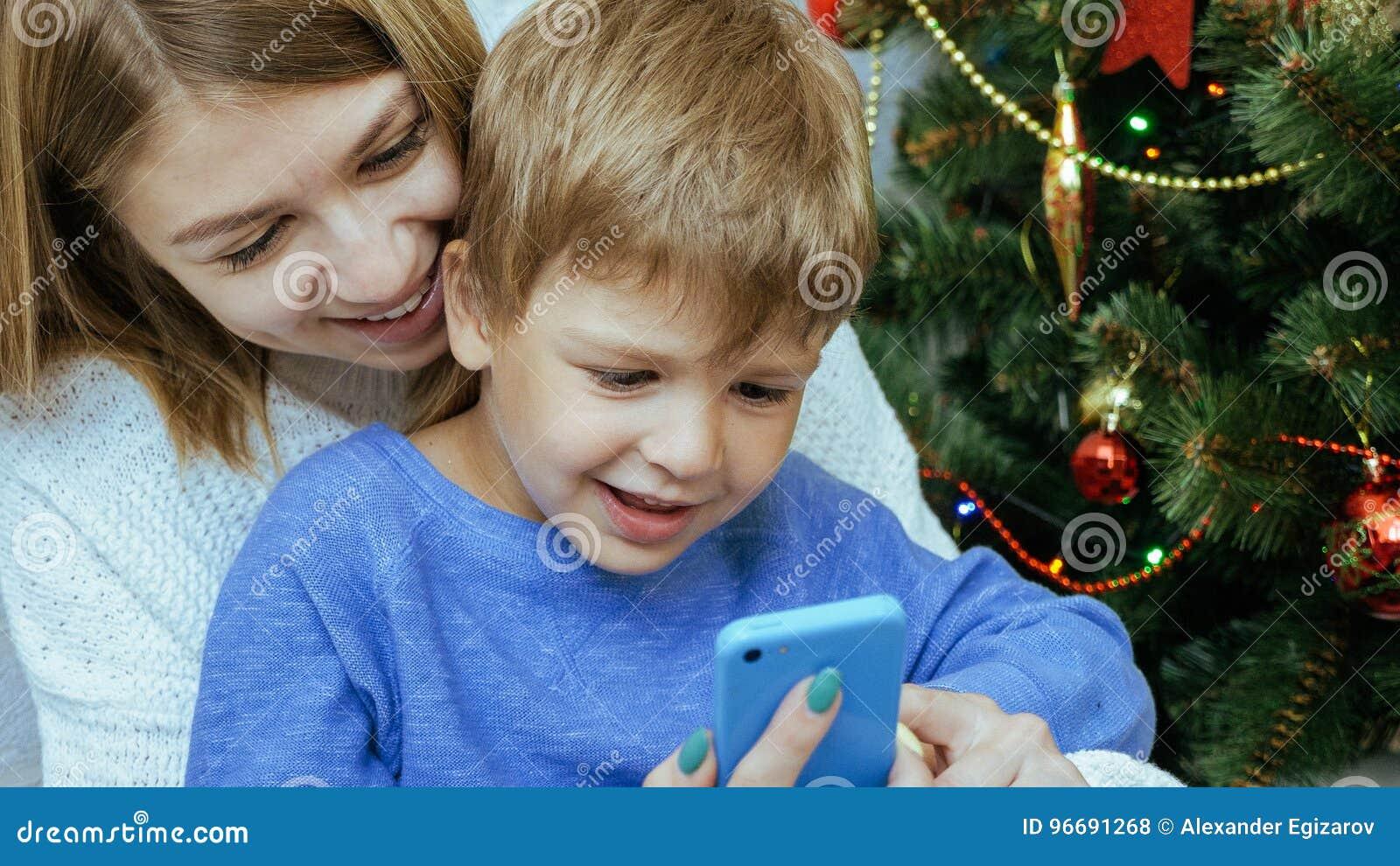 Η μητέρα και ο γιος με το κινητό τηλέφωνο κάθονται μαζί κοντά στο χριστουγεννιάτικο δέντρο