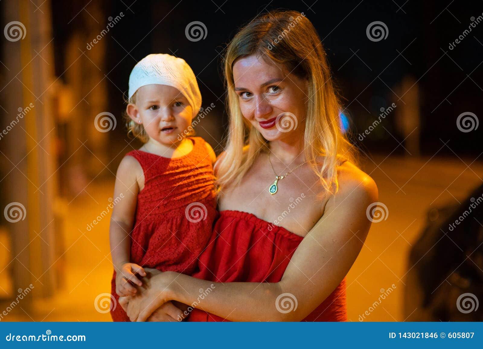 Η μητέρα κρατά την κόρη στα όπλα της, η μητέρα με την κόρη είναι ντυμένη στα κόκκινα φορέματα, παιδί άσπρο beret, τη νύχτα