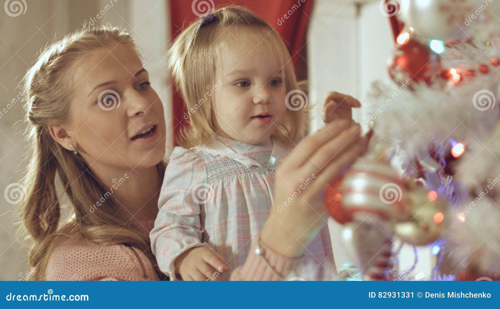 Η μητέρα με το λατρευτό μωρό διακοσμεί ένα χριστουγεννιάτικο δέντρο στο σπίτι