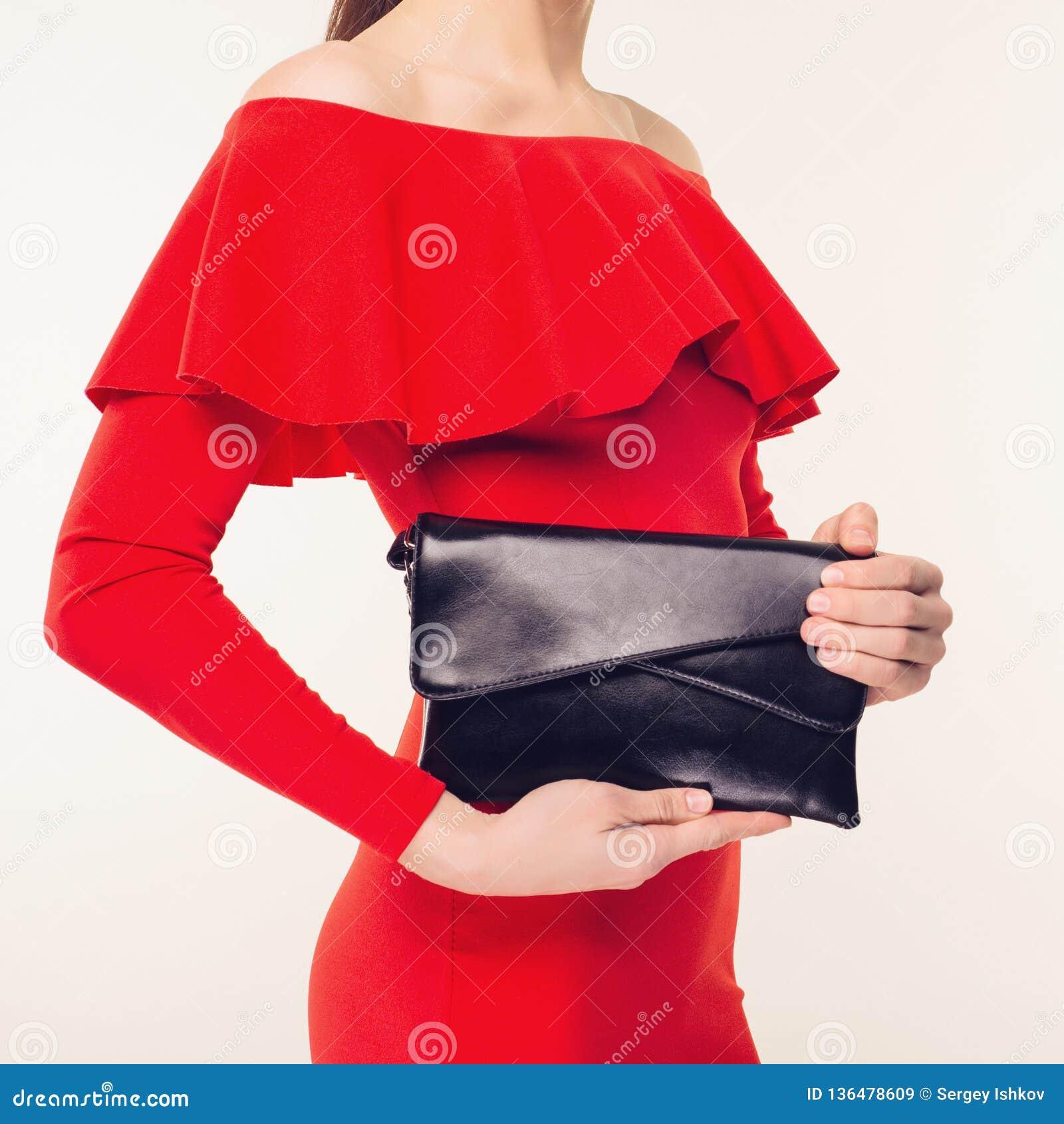 Η μοντέρνη γυναίκα με έναν μαύρο συμπλέκτη στα χέρια της και το κόκκινο βράδυ ντύνουν