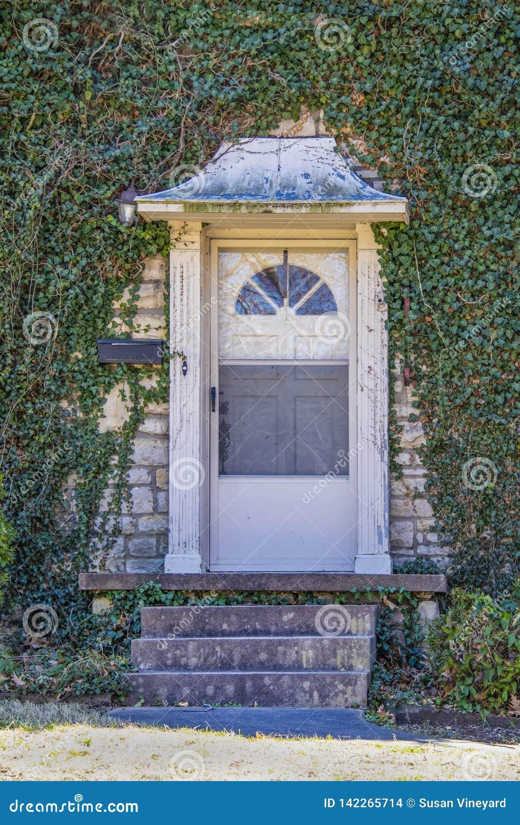 Η μπροστινή πόρτα με awning μετάλλων - παλαιό και φορημένος αλλά όμορφο - έθεσε καλυμμένο στο κισσός σπίτι βράχου - κινηματογράφη