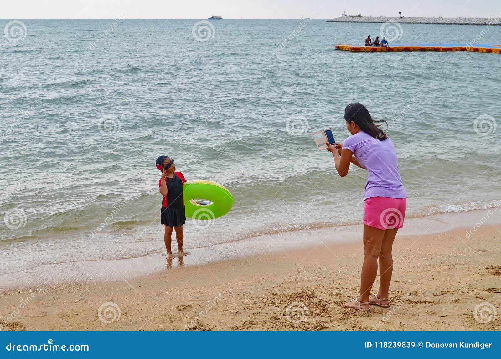 Η νέα ασιατική μητέρα παίρνει μια φωτογραφία της κόρης της στον ωκεανό