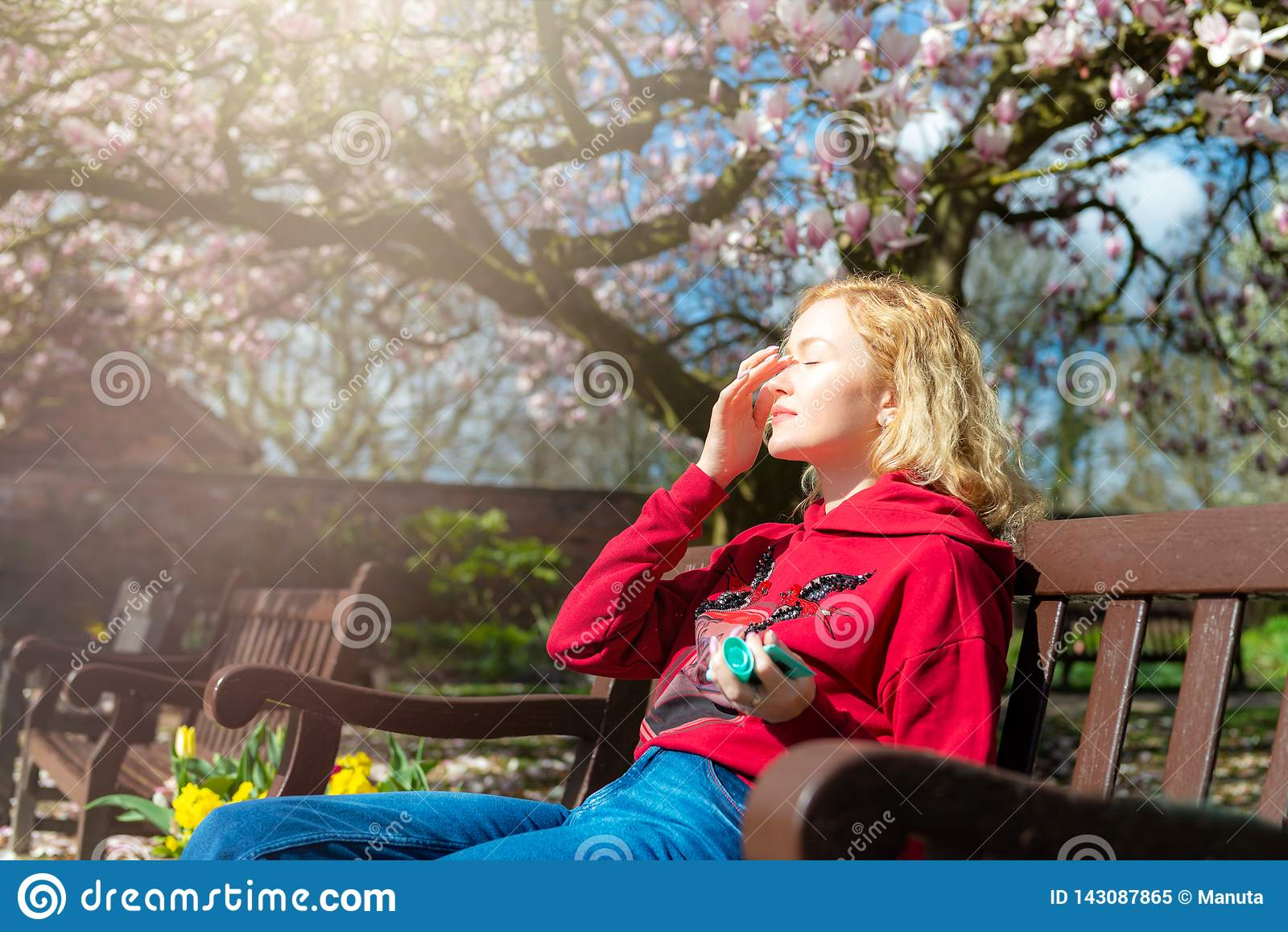 Η νέα γυναίκα εφαρμόζει sunscreen στο πρόσωπό της καθμένος στον πάγκο στο πάρκο