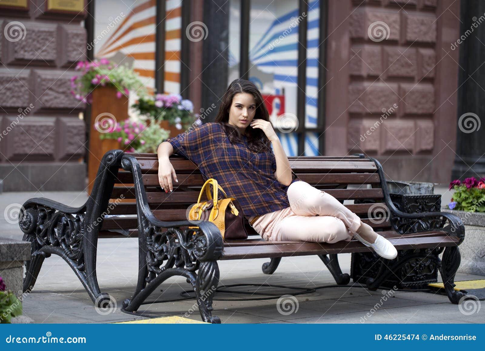 Η νέα γυναίκα κάθεται σε έναν πάγκο στο πόλης κέντρο