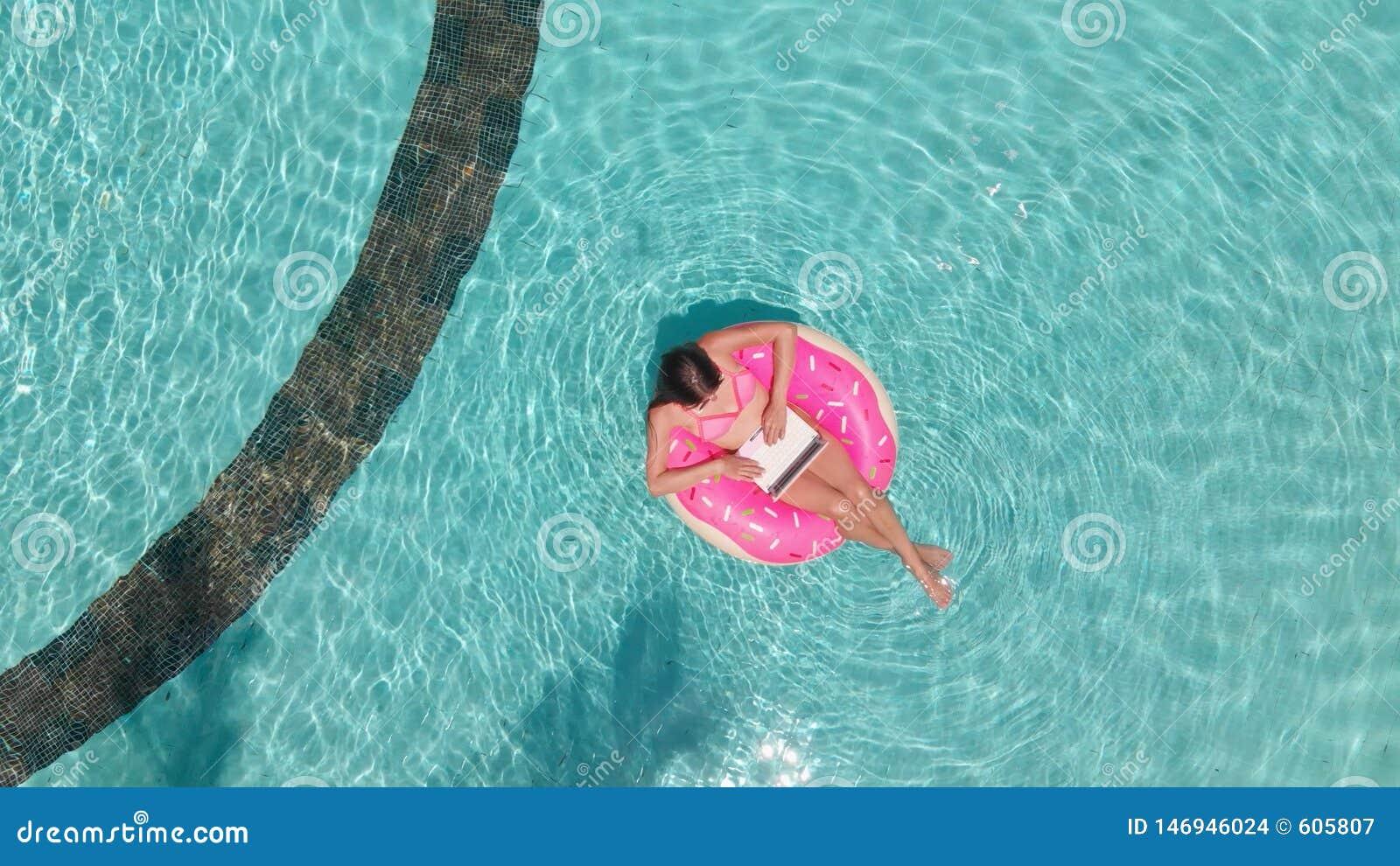 Η νέα γυναίκα κολυμπά στη θάλασσα σε έναν κολυμπώντας κύκλο Κορίτσι που στηρίζεται στη λίμνη σε έναν διογκώσιμο κύκλο με έναν υπο