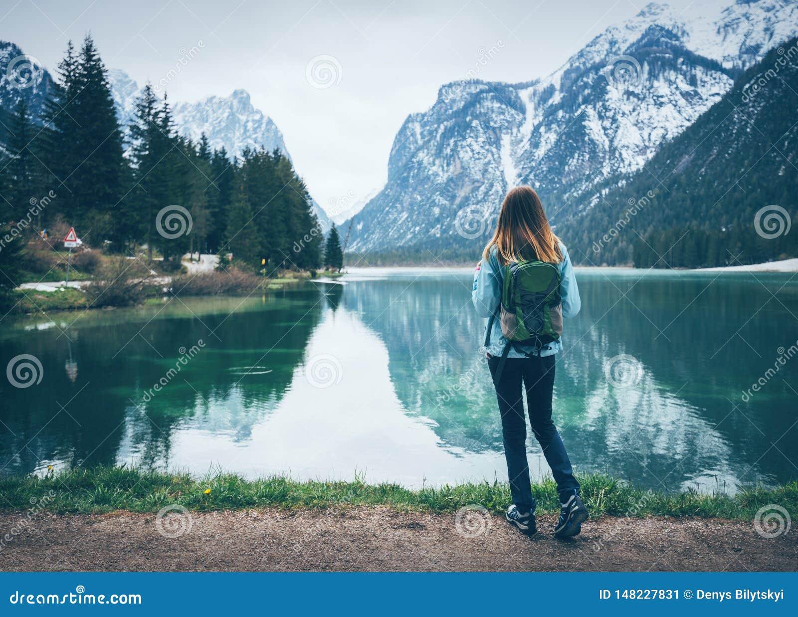 Η νέα γυναίκα με το σακίδιο πλάτης στέκεται στην ακτή της λίμνης
