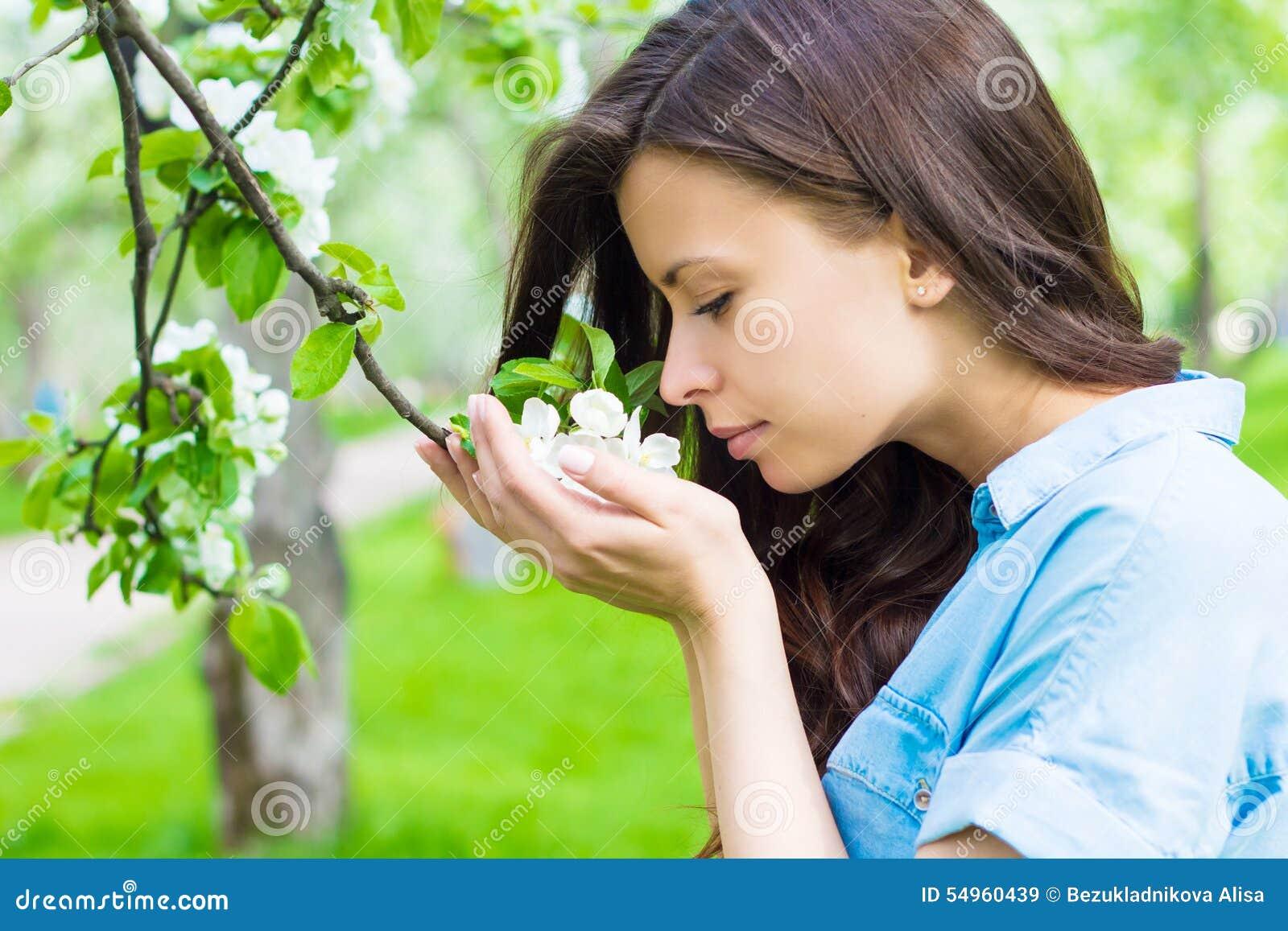 Η νέα γυναίκα μυρίζει το λουλούδι μήλων