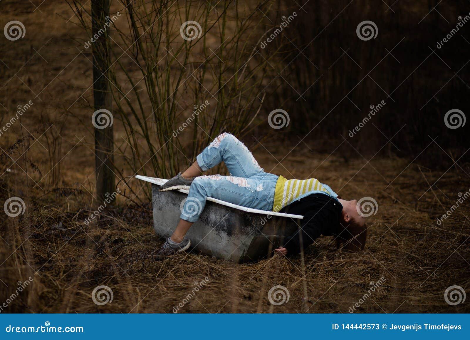Η νέα γυναίκα στα ενδύματα παίρνει ένα κενό παλαιό λουτρό στη μέση ενός δάσους
