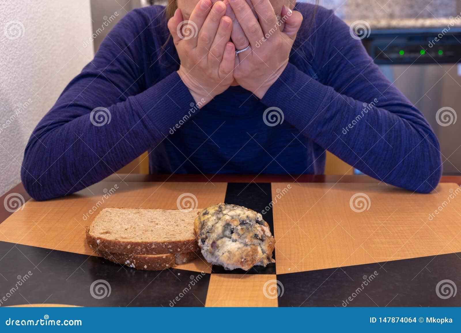 Η νέα γυναίκα φωνάζει και θάβει το κεφάλι και το πρόσωπό της καθμένος σε έναν πίνακα κουζινών με μια έννοια scone και φρυγανιάς γ