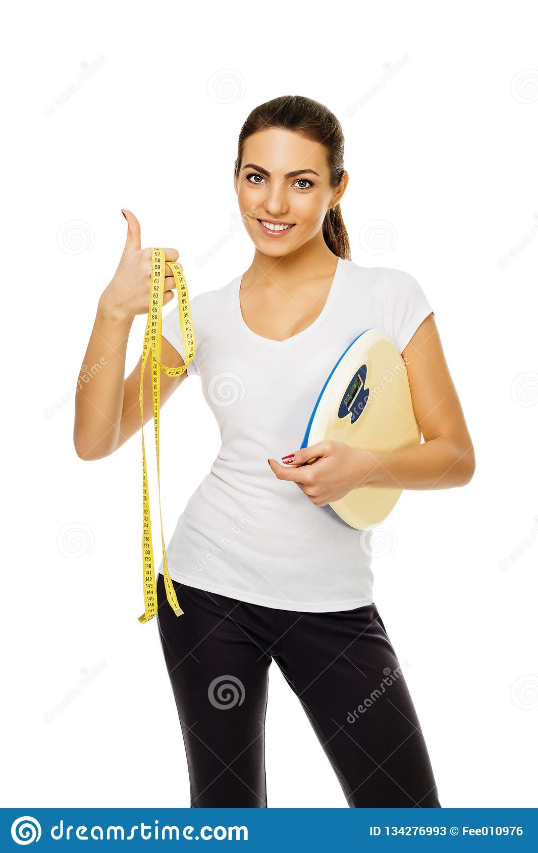 Η νέα γυναίκα brunette στην άσπρη μπλούζα κρατά τις κλίμακες και η ταινία δίνει τους αντίχειρες επάνω στέκεται το χαμόγελο στο άσ