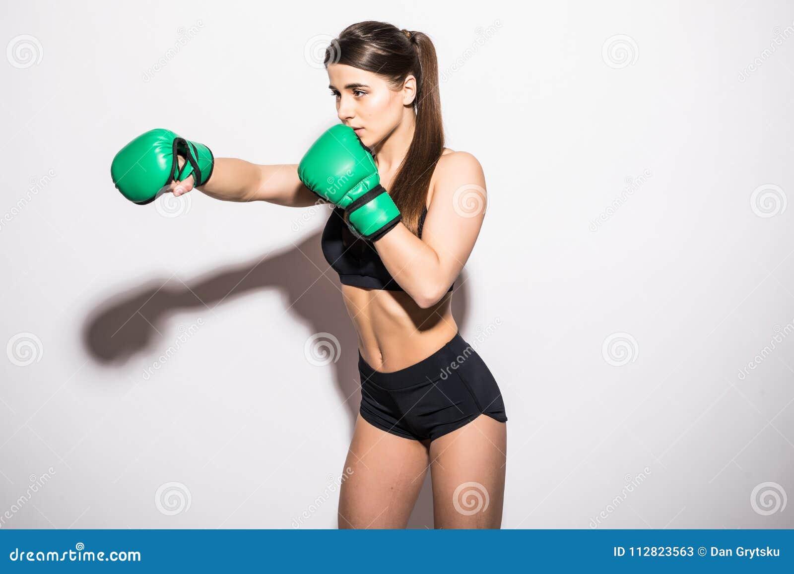 Η νέα γυναίκα sportswear και τα πράσινα εγκιβωτίζοντας γάντια χαμογελά σε ένα απομονωμένο λευκό υπόβαθρο