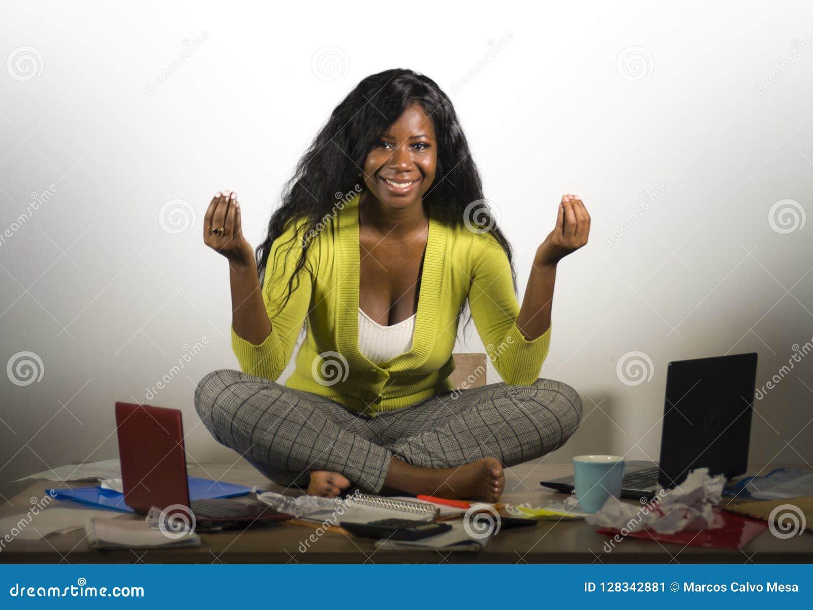 Η νέα ευτυχής και ελκυστική επιχειρησιακή γυναίκα αφροαμερικάνων που κάνει τη συνεδρίαση γιόγκας στο ακατάστατο σύνολο γραφείων γ
