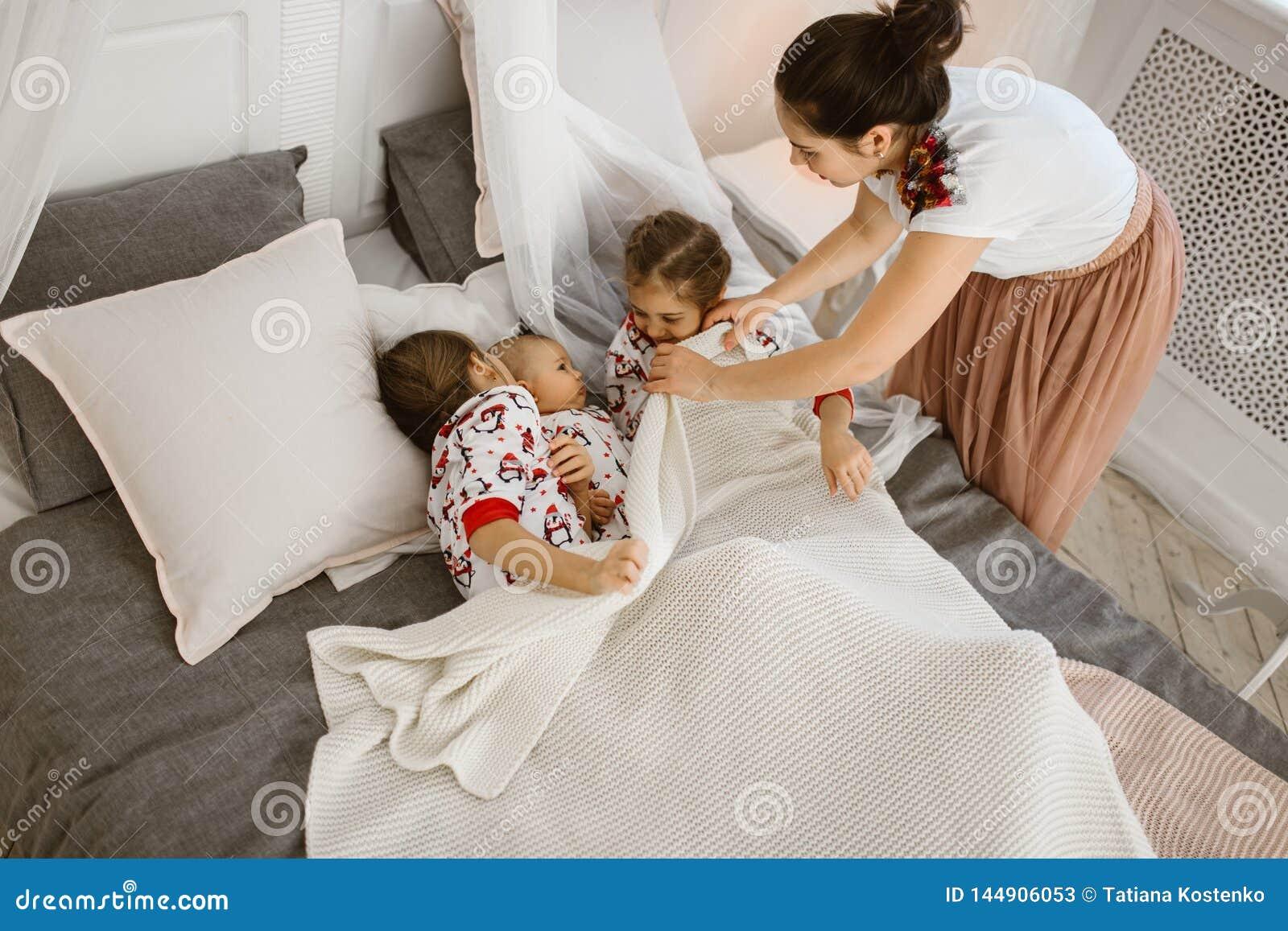 Η νέα μητέρα καλύπτει ένα άσπρο κάλυμμα για δύο κόρες και έναν μικροσκ