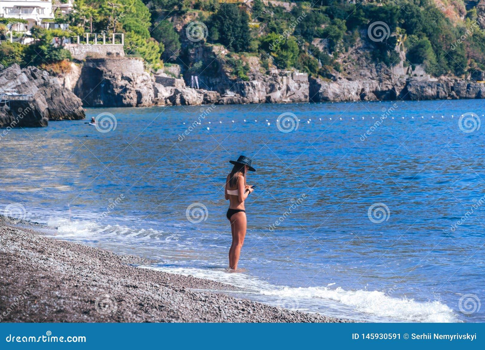 Η νέα στάση γυναικών μόνο στην παραλία και εξετάζει το τηλέφωνό της Καλό, κακό σήμα έννοιας
