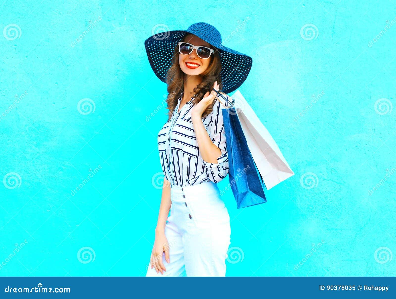 Η νέα χαμογελώντας γυναίκα πορτρέτου μόδας που φορά αγορές τοποθετεί σε σάκκο, καπέλο αχύρου, άσπρα εσώρουχα πέρα από τη ζωηρόχρω