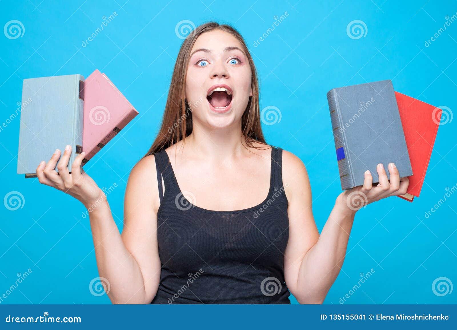 Η νέα όμορφη γυναίκα με 2 βιβλία σε κάθε ένα δίνει τις κραυγές με τις ισχυρές συγκινήσεις με το στόμα επάνω