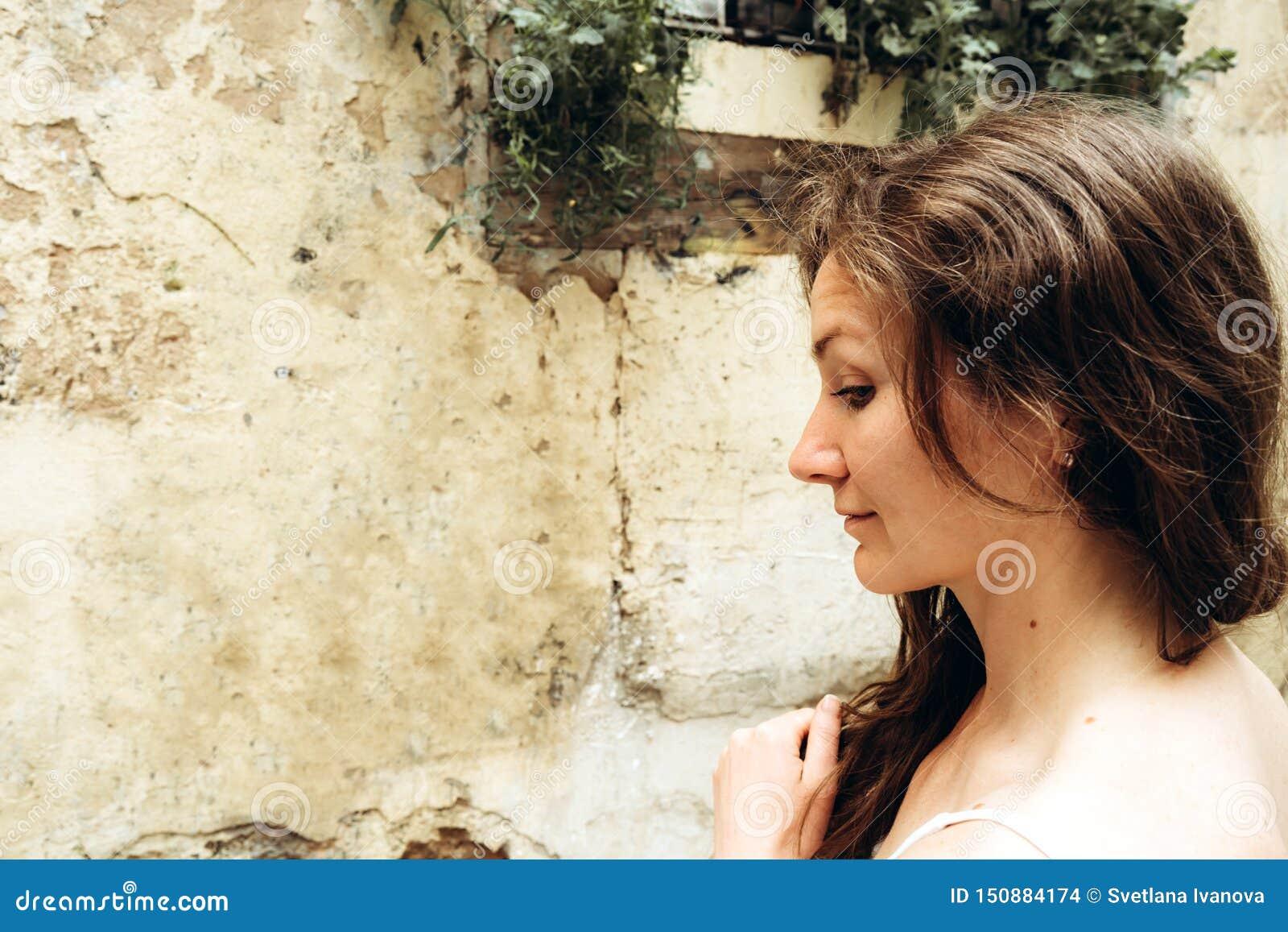 Η νέα όμορφη γυναίκα μια θερινή ημέρα στέκεται στο σχεδιάγραμμα