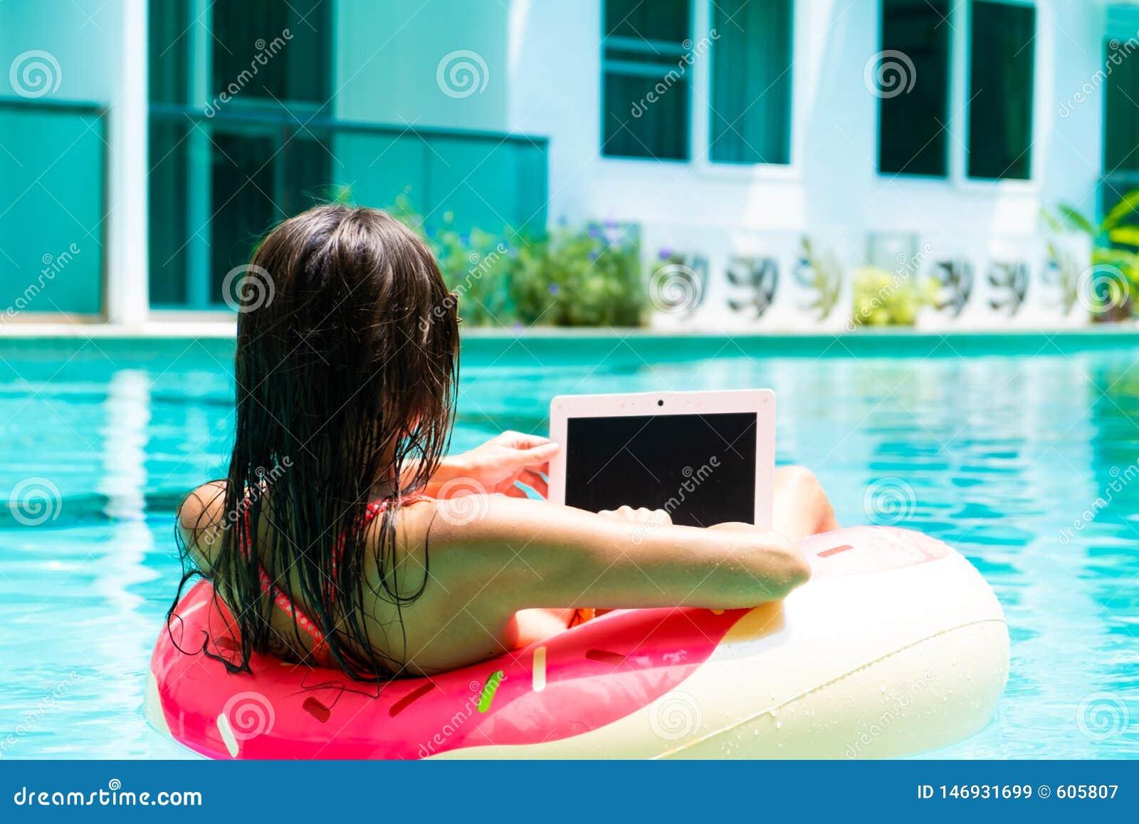 Η νέα όμορφη γυναίκα freelancer επιπλέει στη θάλασσα ή στη λίμνη σε έναν κολυμπώντας κύκλο Ένα κορίτσι χαλαρώνει