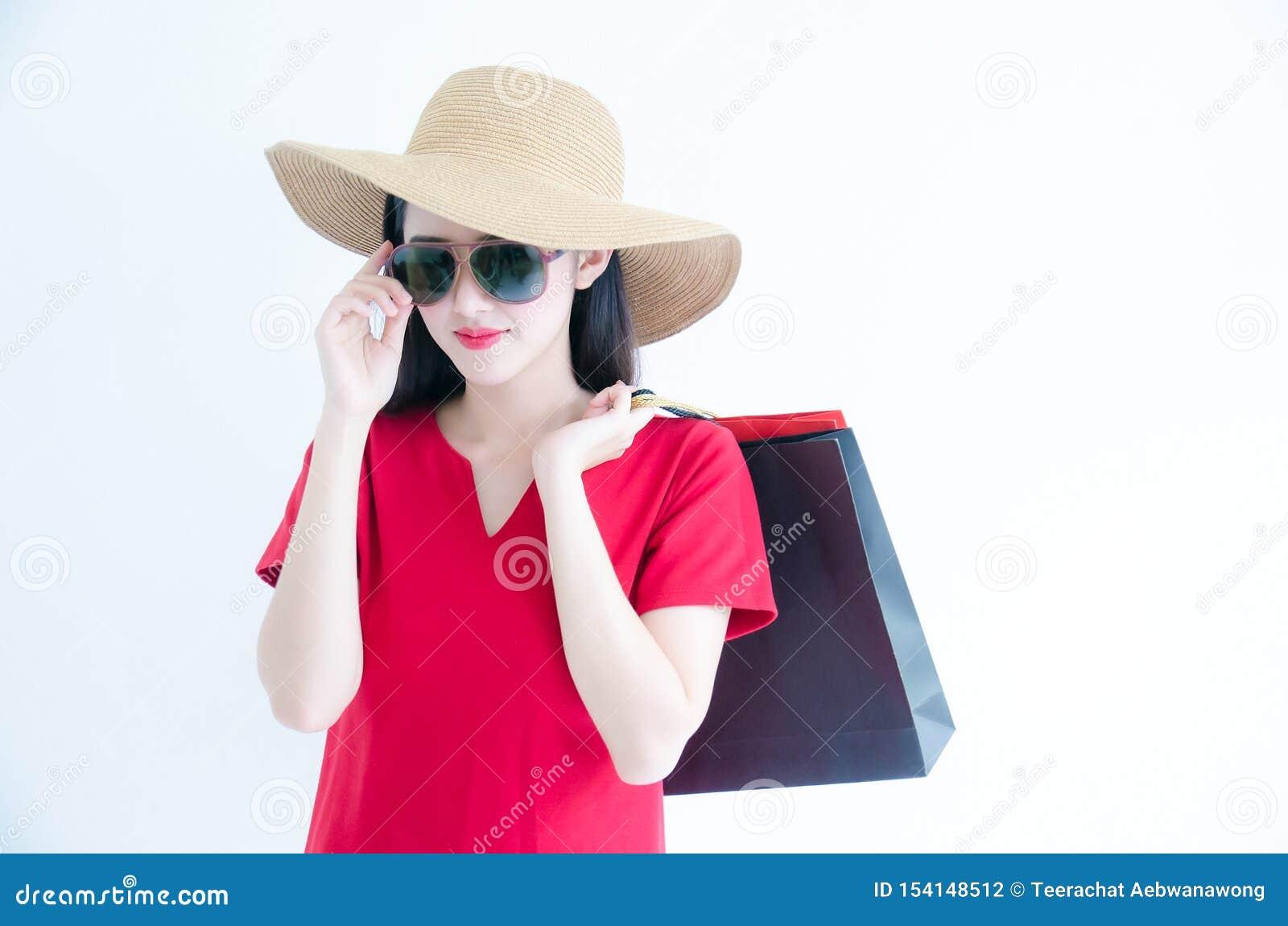 Η νέα όμορφη μοντέρνη ασιατική εκμετάλλευση γυναικών που ψωνίζει τοποθετεί τη φθορά του κόκκινων φορέματος, των γυαλιών ηλίου και