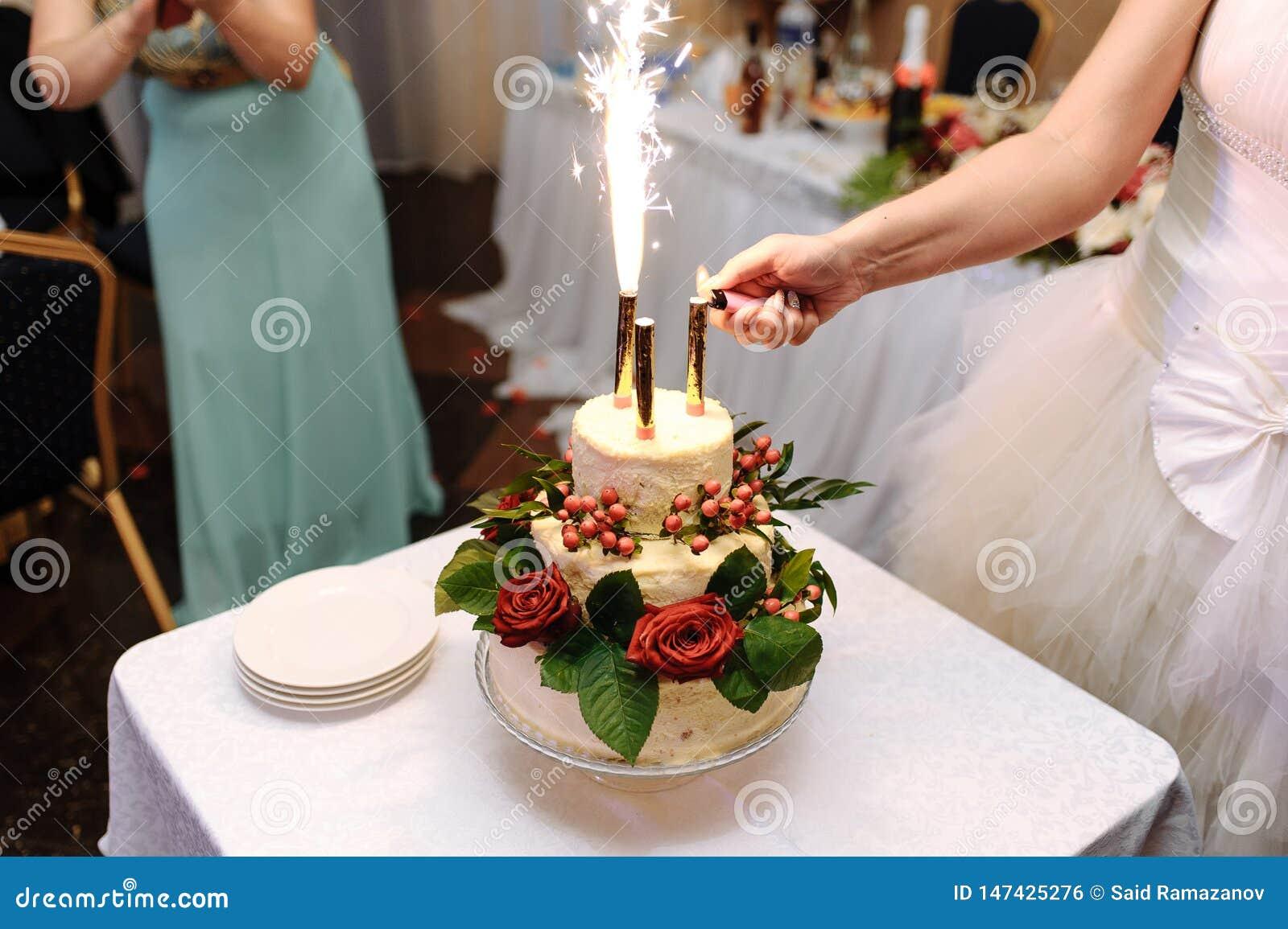 Η νύφη ανάβει τα πυροτεχνήματα στο γαμήλιο κέικ σε ένα ελαφρύ τραπεζομάντιλο