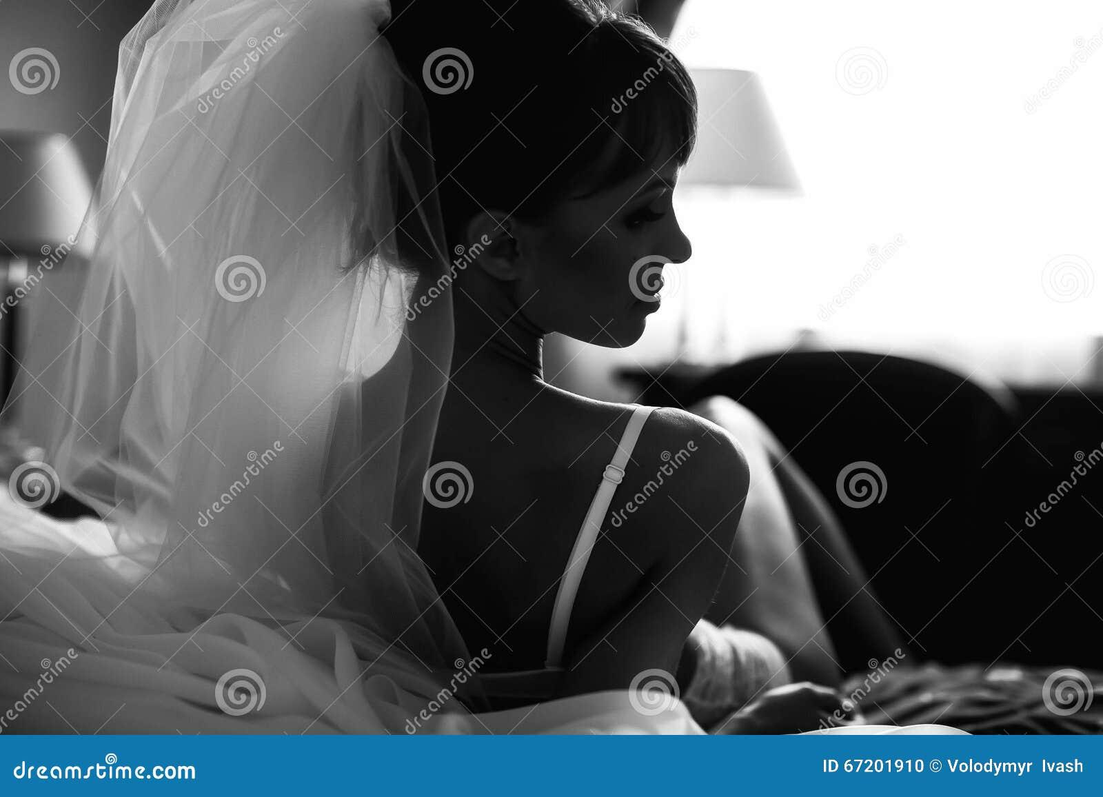 Η νύφη θέτει στη λευκότητα στο κρεβάτι υποβάθρου