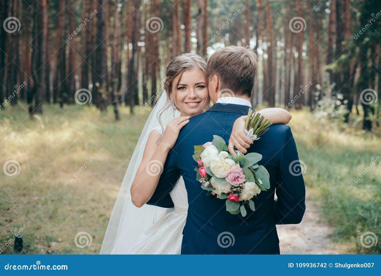 Η νύφη και ο νεόνυμφος στο γάμο ντύνουν στο φυσικό υπόβαθρο ευτυχής εκλεκτής ποιότητας γάμος ημέρας ζευγών ιματισμού Το Newlyweds