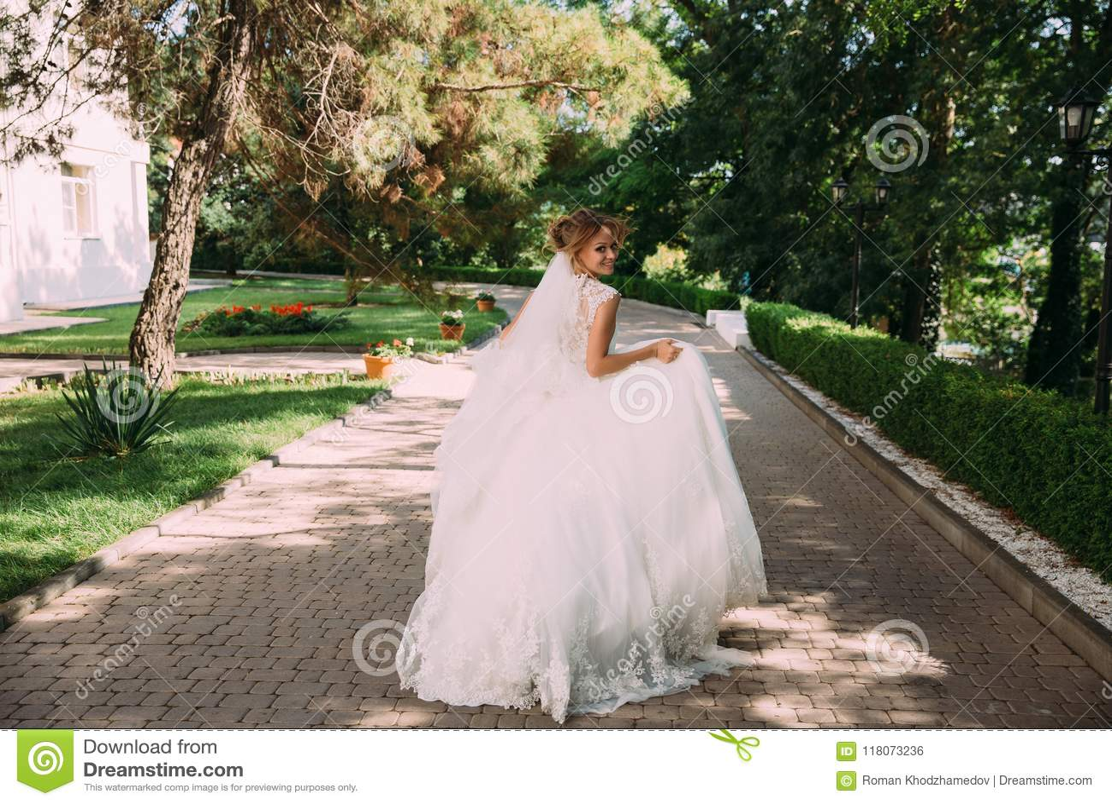 Η νύφη τρέχει παιχνιδιάρικα κατά μήκος της αλέας των πετρών Το κορίτσι στο γαμήλιο φόρεμα έχει τη διασκέδαση και τρέχει μακριά