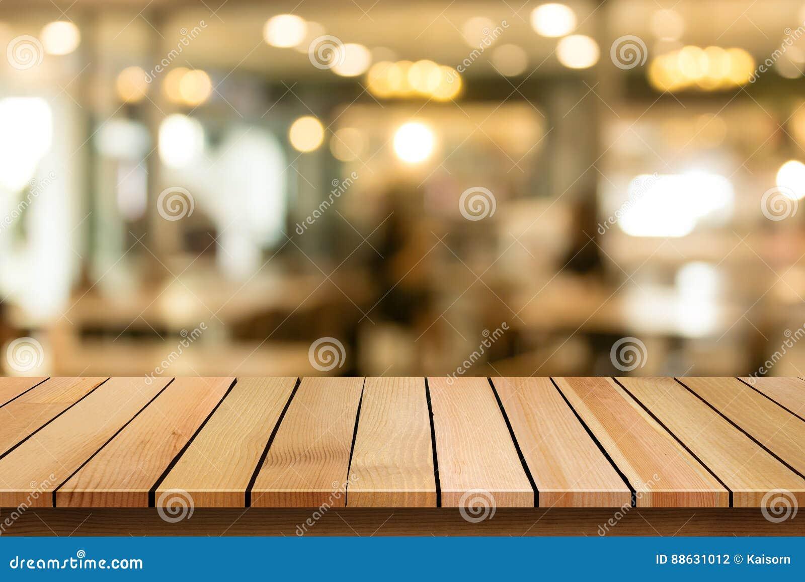 Η ξύλινη επιτραπέζια κορυφή στο υπόβαθρο καφέδων θαμπάδων bokeh μπορεί να χρησιμοποιηθεί για το DIS