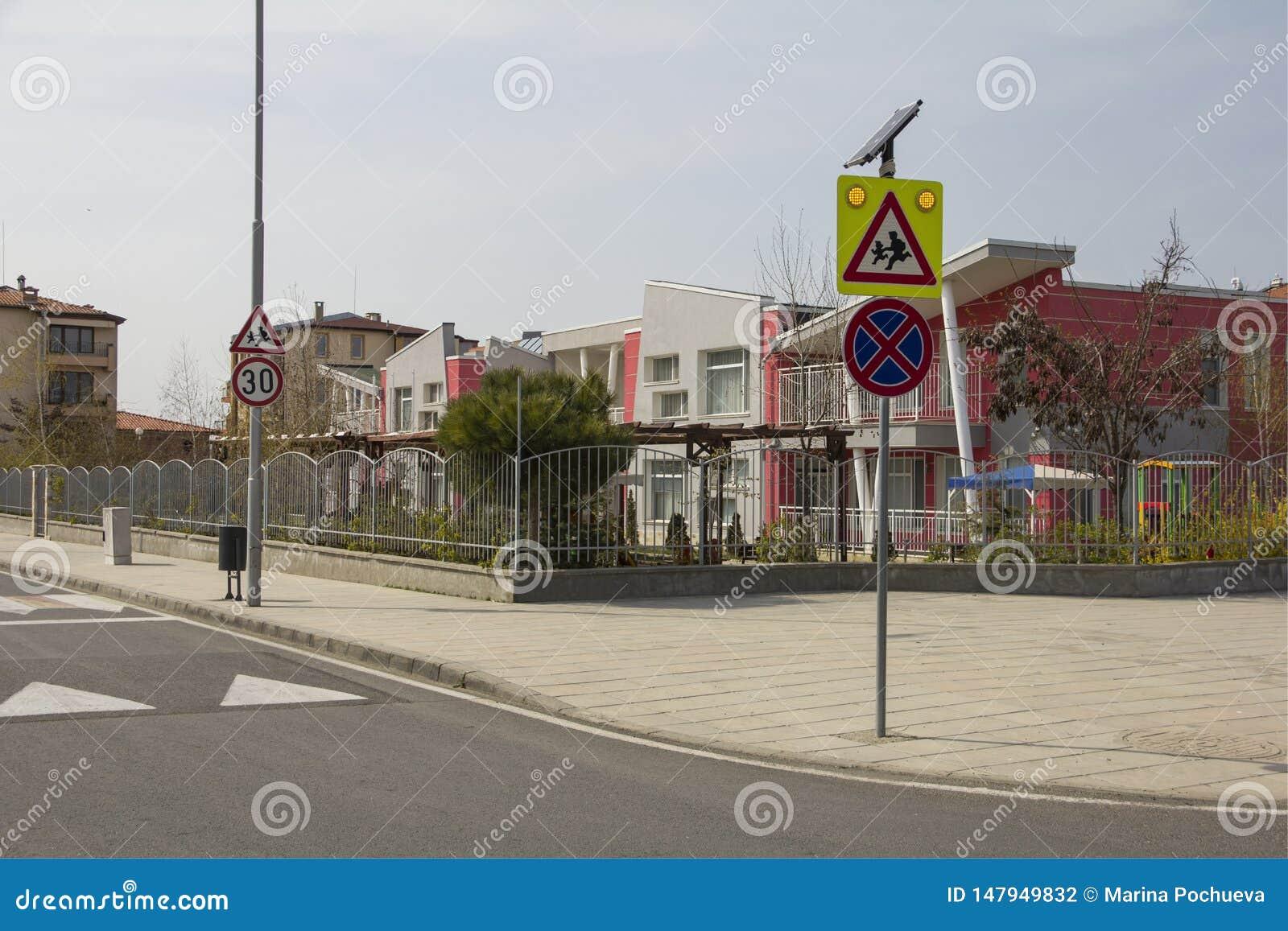 """Η οδός πόλεων με ένα για τους πεζούς πέρασμα, μια πρόσκρουση ταχύτητας και μια προσοχή υπογράφουν """"τα παιδιά """"κοντά σε έναν όμορφ"""