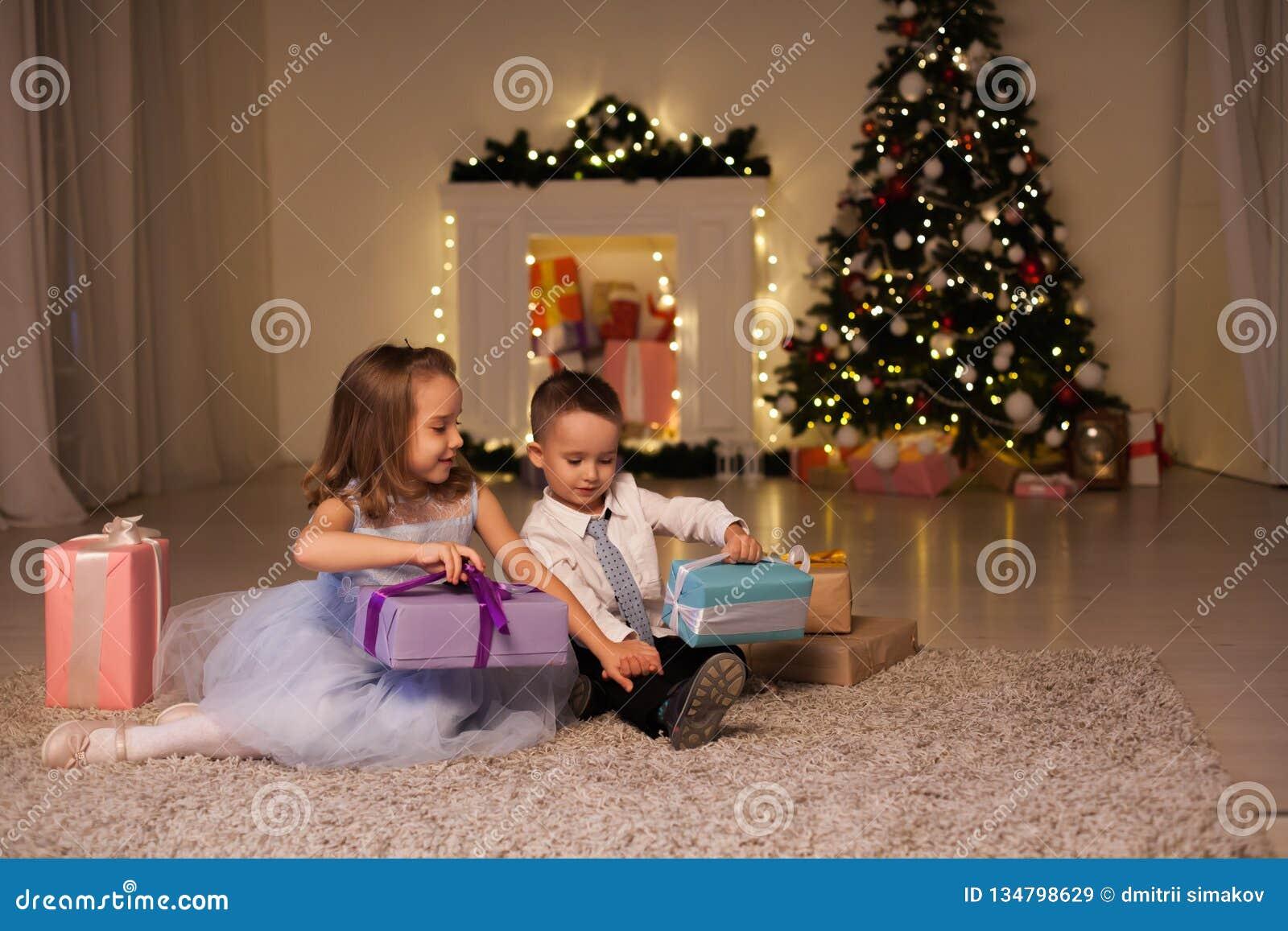 Η οικογένεια αγοριών και κοριτσιών ανοίγει τις νέες γιρλάντες χριστουγεννιάτικων δέντρων φω των διακοπών έτους δώρων Χριστουγέννω