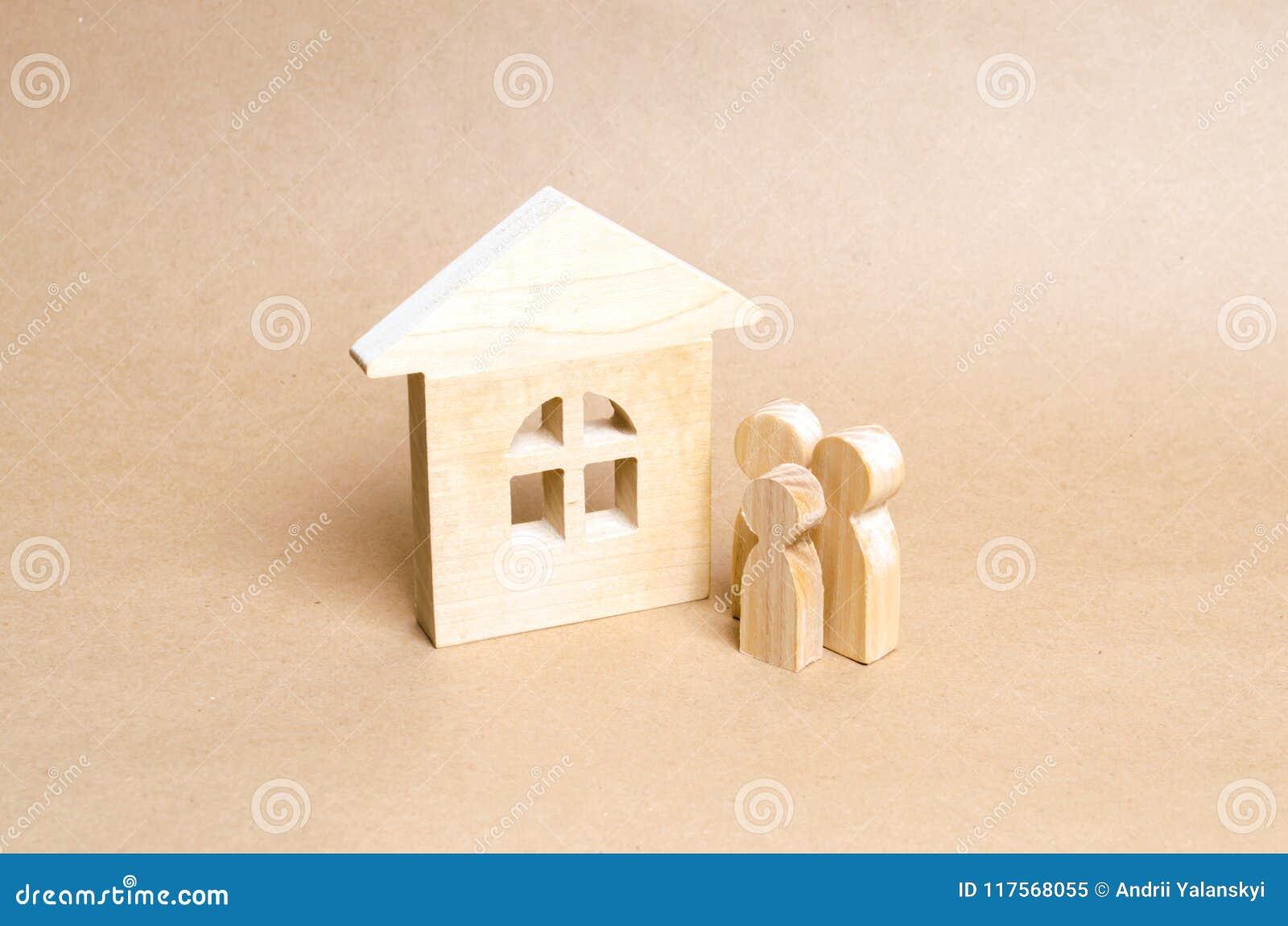 Η οικογένεια στέκεται κοντά σε ένα ξύλινο σπίτι Μερικοί νέοι στέκονται κοντά στο νέο σπίτι τους Αγορά και πώληση της κατοικίας