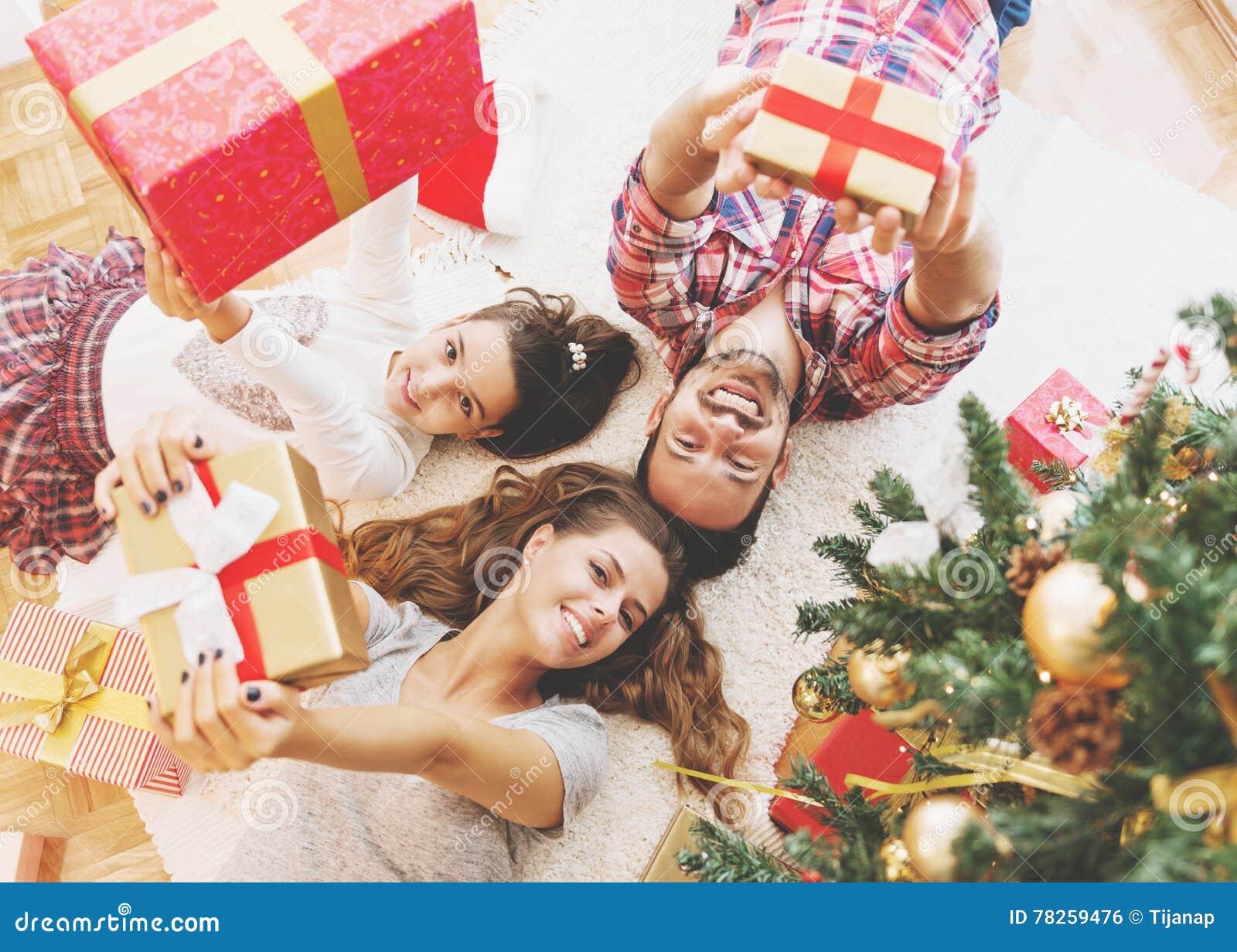 Η οικογένεια συλλέγει γύρω από ένα χριστουγεννιάτικο δέντρο, το κράτημα παρουσιάζει