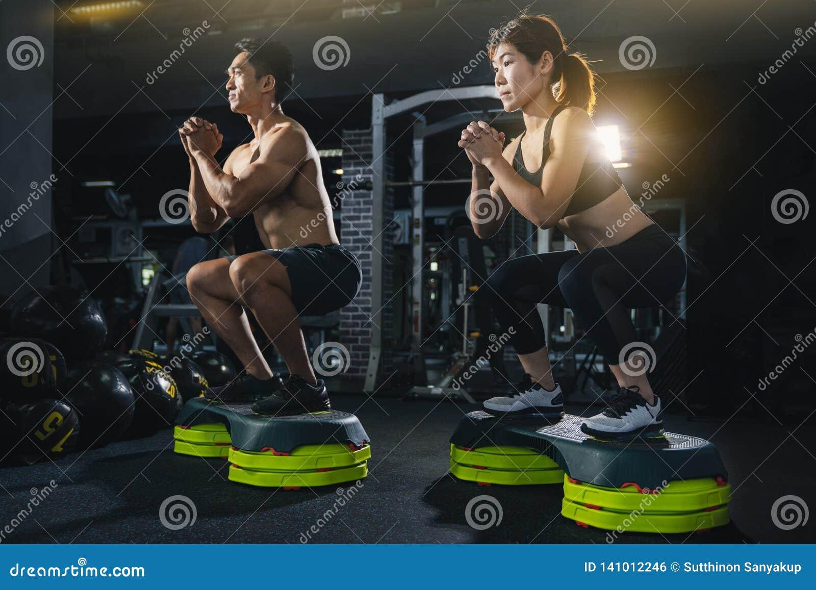 Η ομάδα υγιών ανθρώπων ικανότητας στη γυμναστική, νέο ζεύγος επιλύει στη γυμναστική, η ελκυστική γυναίκα και ο όμορφος μυϊκός άνδ